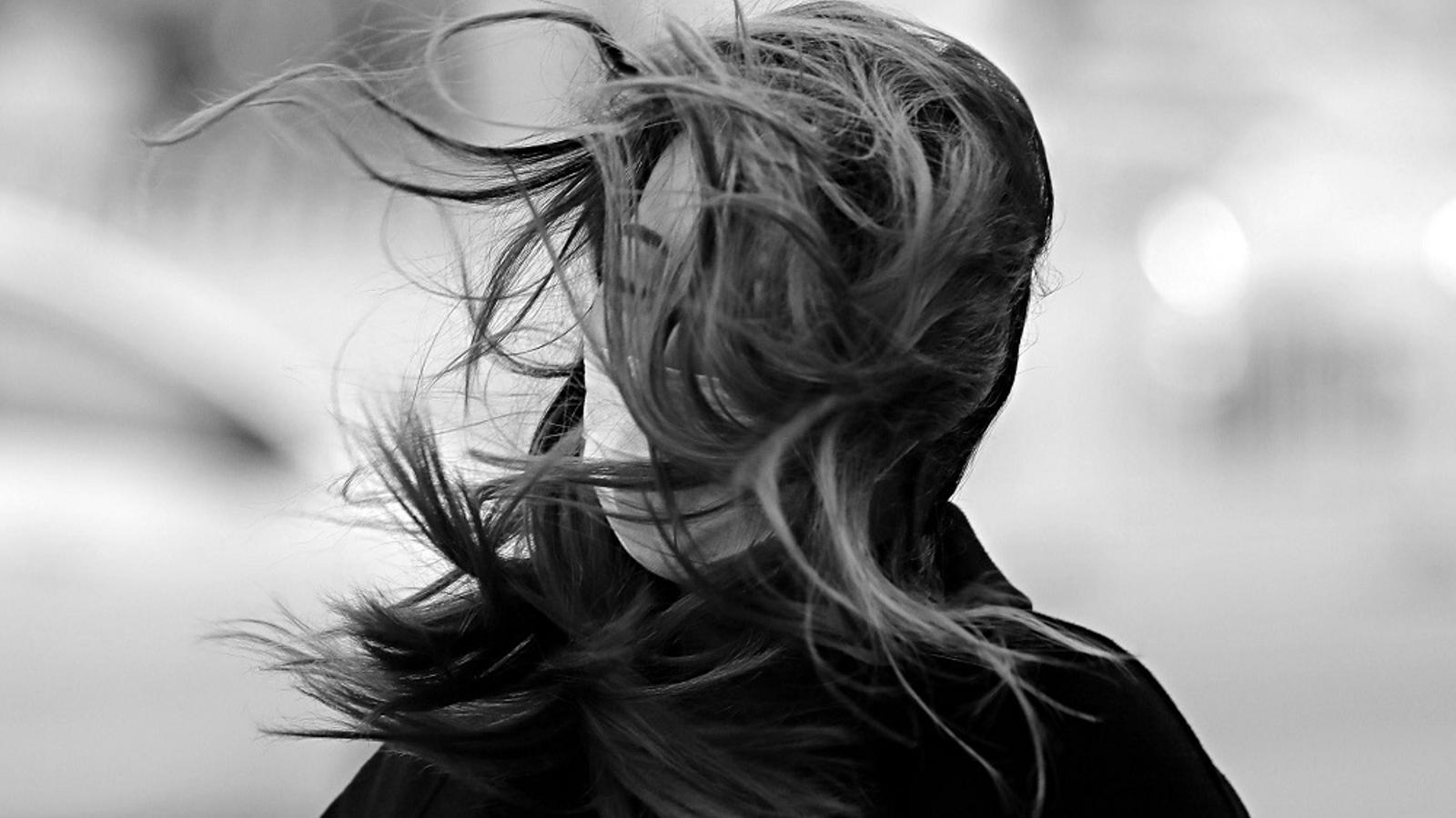 Una dona amb mascareta rep una ventada que li desordena els cabells, a Pequín, el 18 de març de 2020.