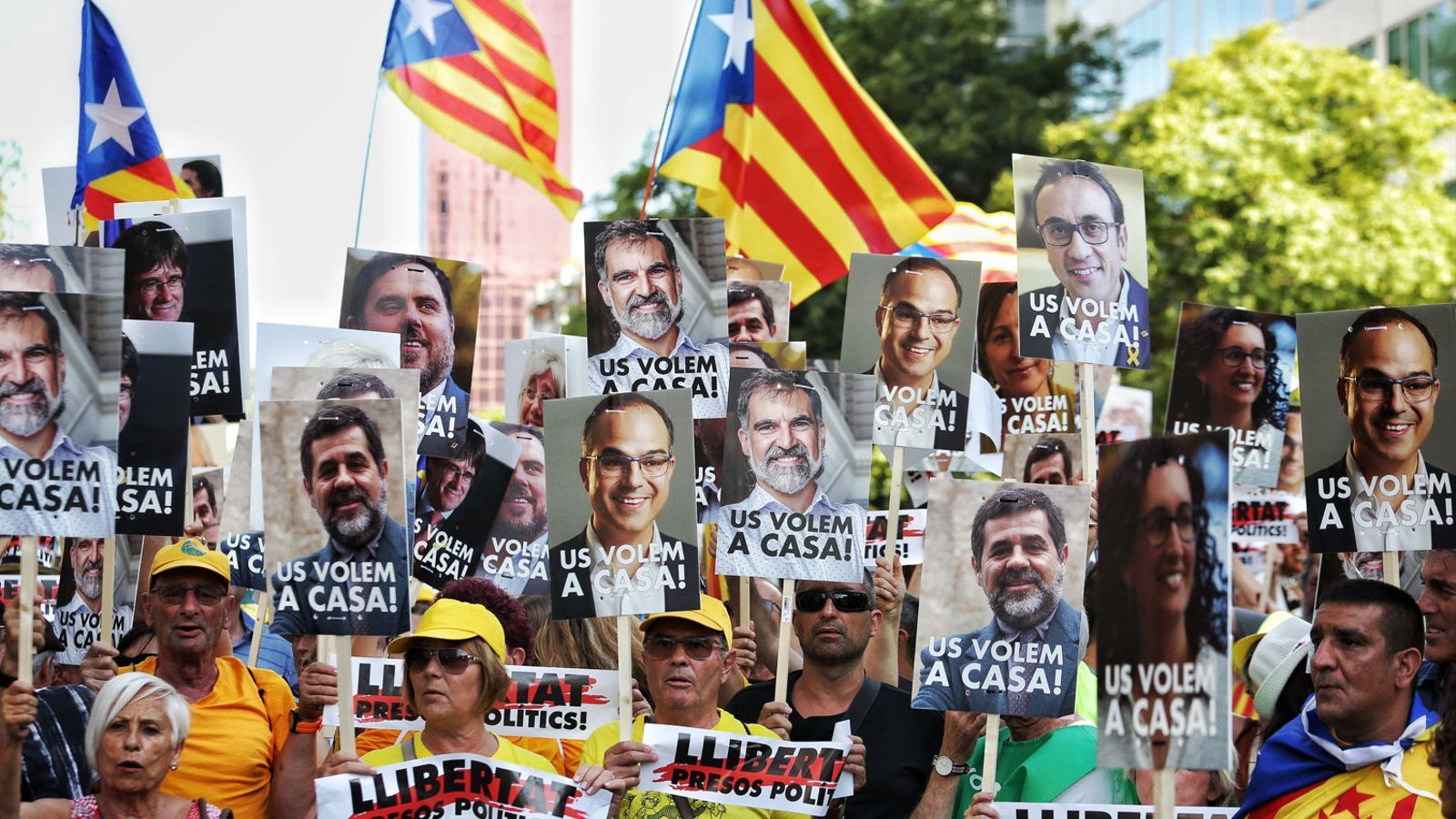 Un grup de manifestants sostenen pancartes amb fotografies dels presos i exiliats, dissabte a Barcelona.