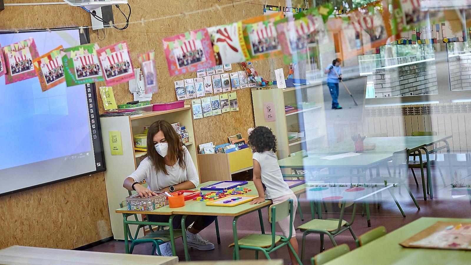 Una mestra amb mascareta i una alumna a l'Institut Escola Vila-romà de Palamós.