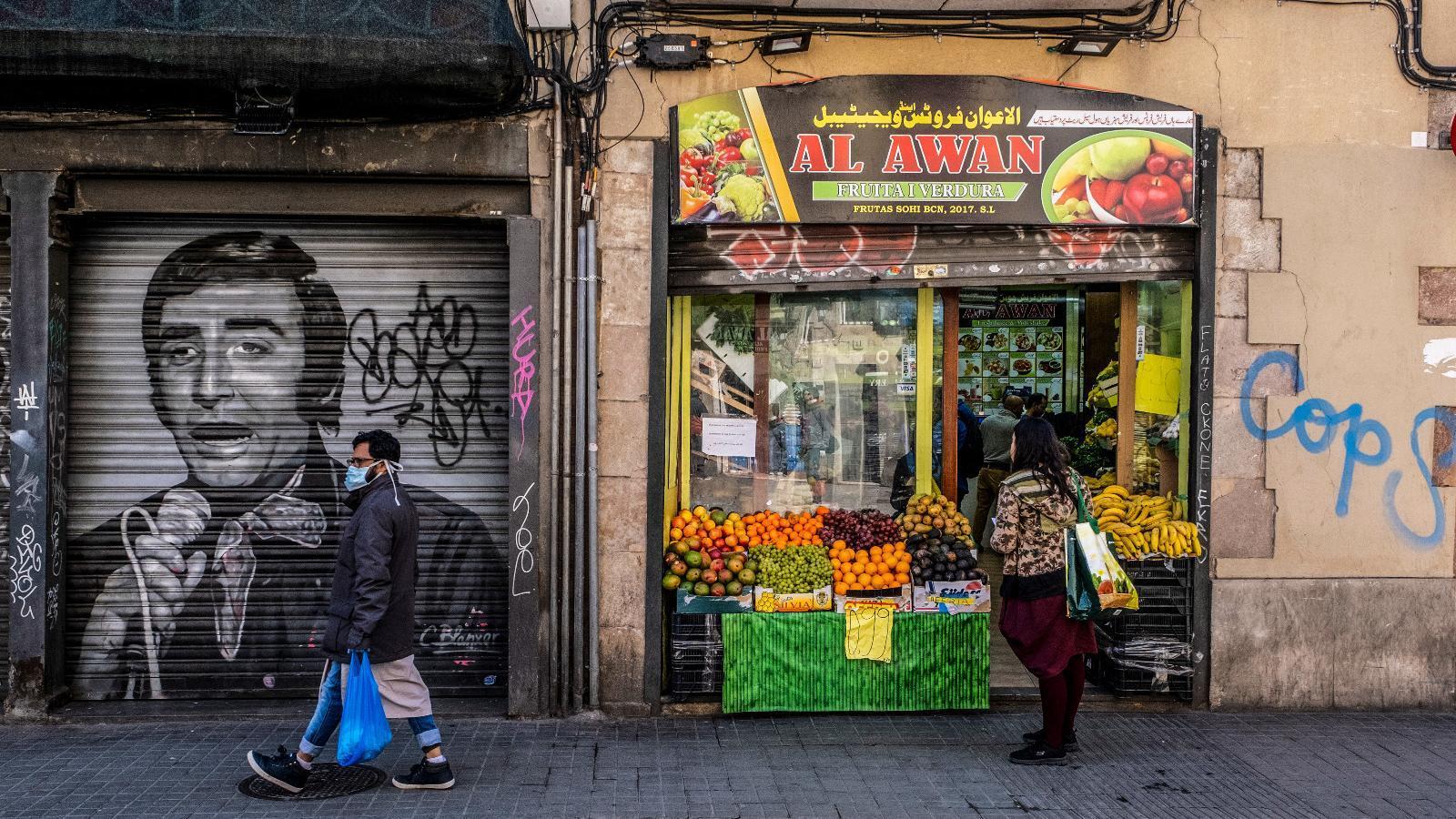 Un home passava, aquest dilluns, per davant d'un mural del Peret, a la plaça del Pedró, al Raval.