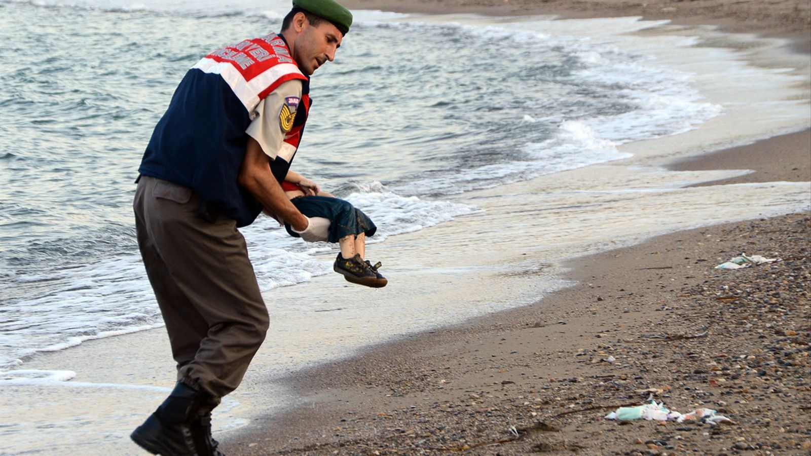 Un gendarme turc s'endú un dels nens que anaven en una de les barques amb què diversos refugiats intentaven arribar a Grècia per Turquia / REUTERS