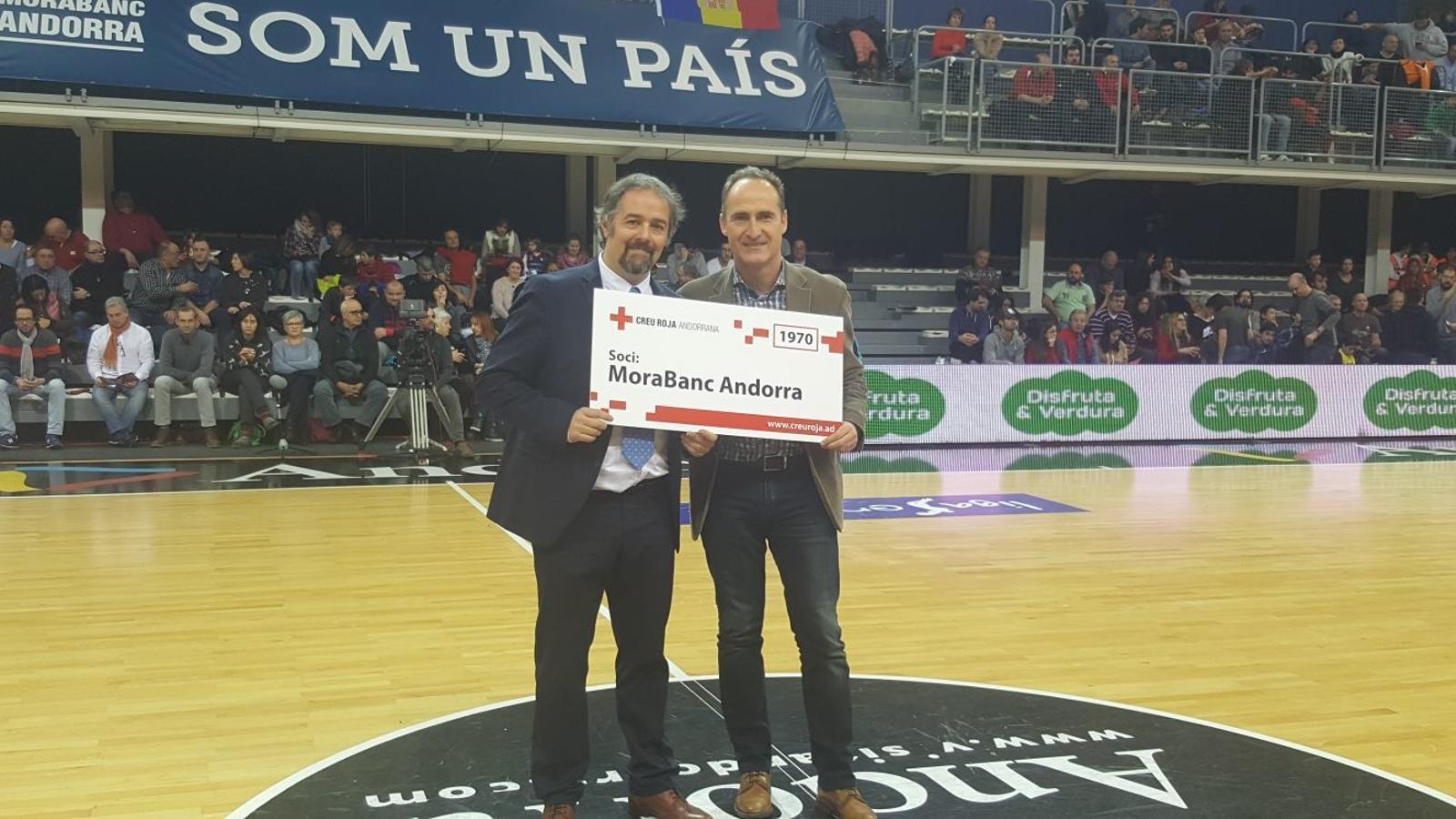 El vicepresident de la Creu Roja, David Fraissinet, entrega un carnet de soci simbòlic al cap de premsa del MoraBanc Andorra, Gabi Fernádez. / CREU ROJA ANDORRANA