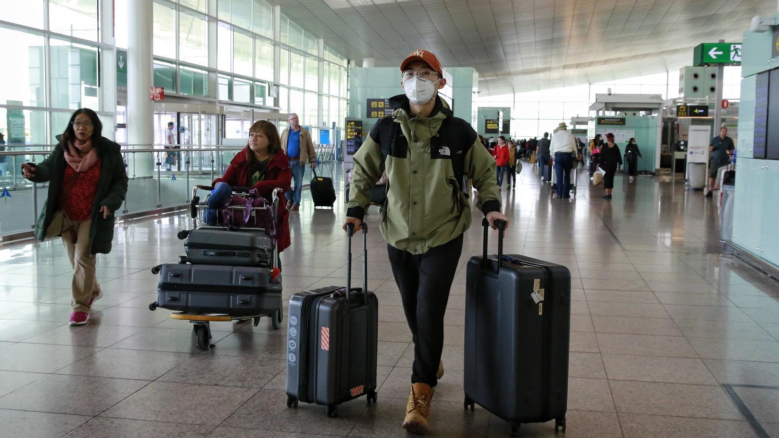 Viatgers, amb mascaretes pel coronavirus, a la terminal de sortides de l'aeroport del Prat, aquest matí