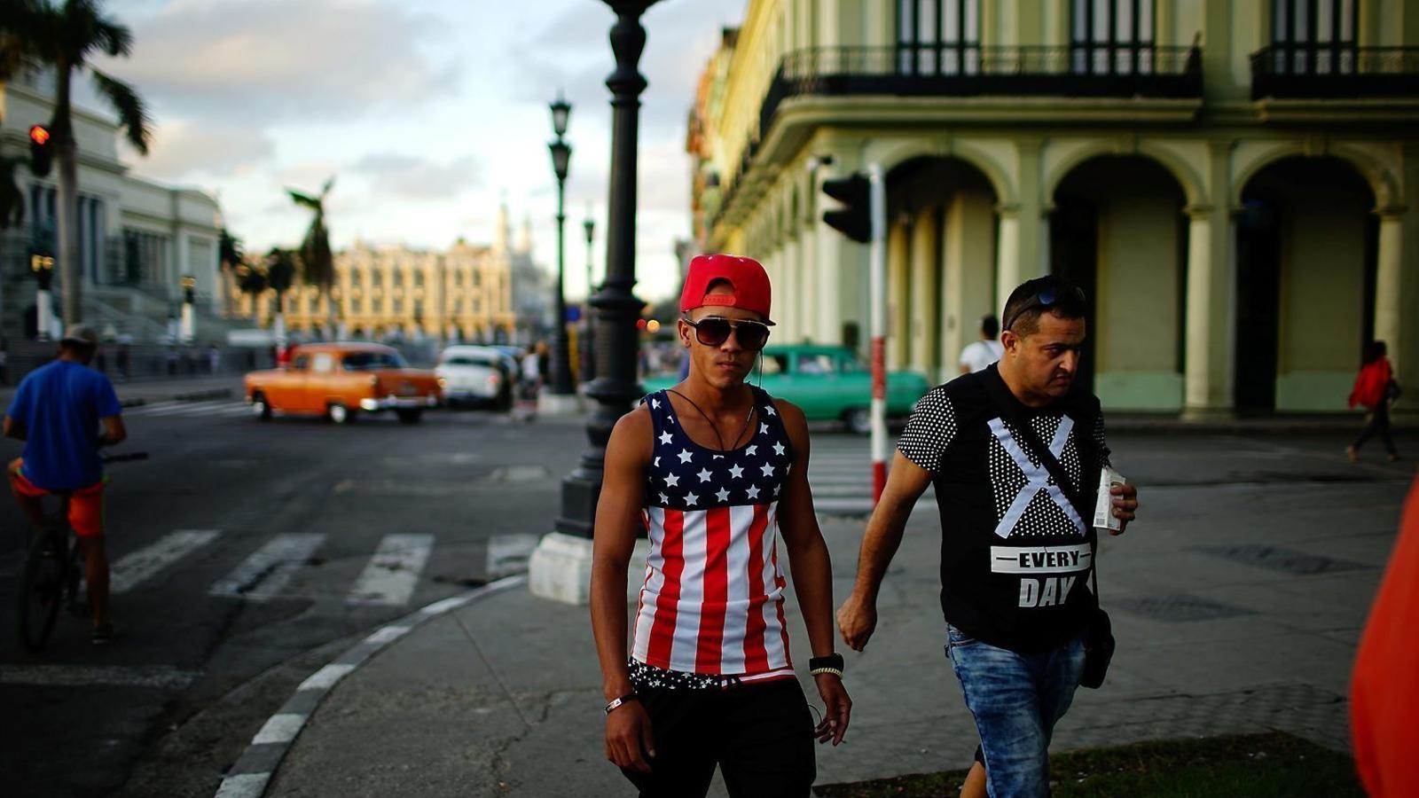 Un jove cubà vestit amb la samarreta nord-americana es passeja pel centre de l'Havana.