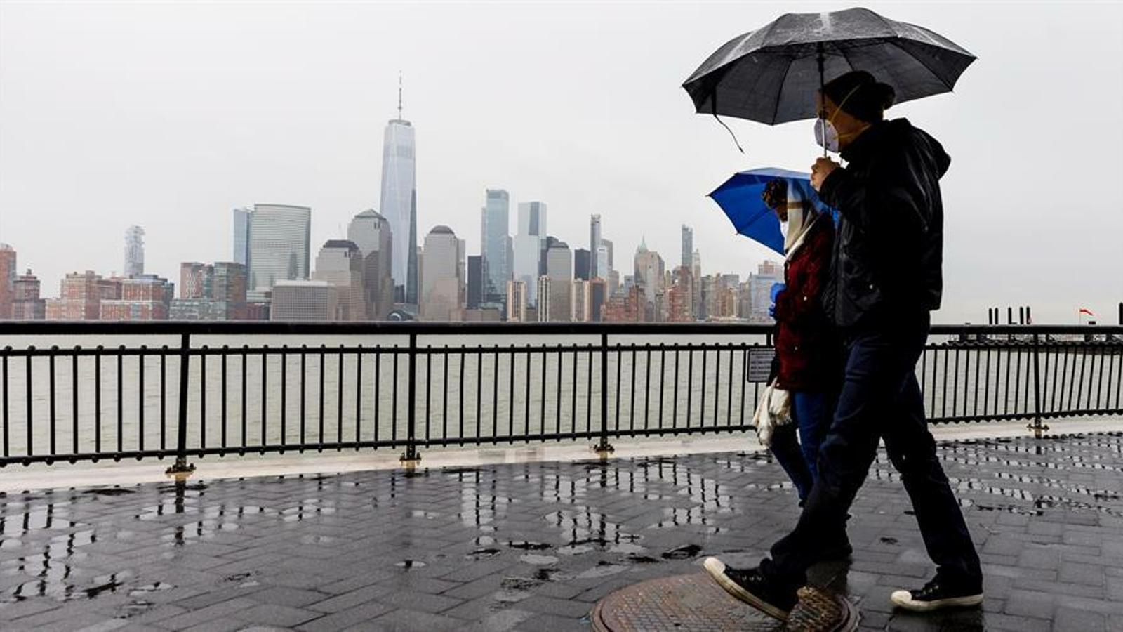 Una parella amb mascareta i paraigua caminant per un passeig amb Manhattan al davant