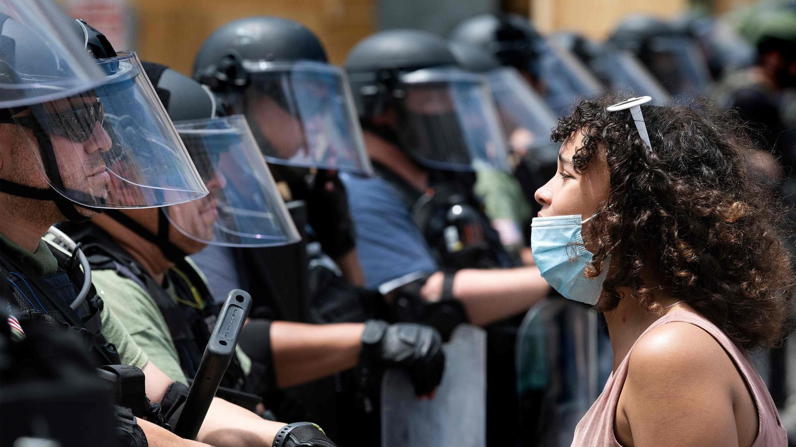 Una manifestant davant de desenes d'agents desplegats davant de la Casa Blanca, a Washington