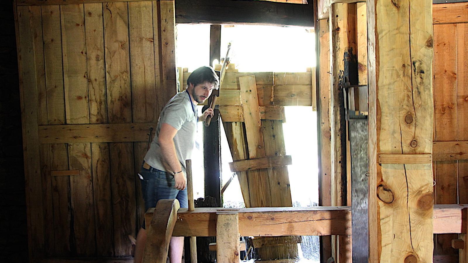 El guia turístic de la mola i serradora de Cal Pal fa una demostració sobre el seu funcionament. / C. G. (ANA)