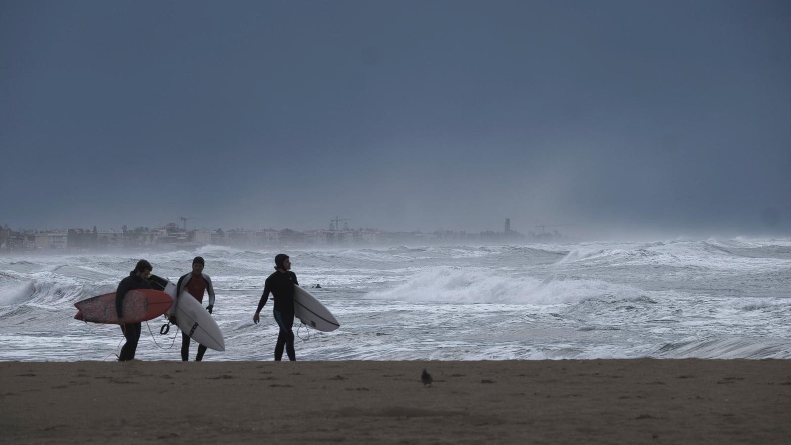 Tres surfistes aprofitant les onades del temporal, a la platja de Castelldefels