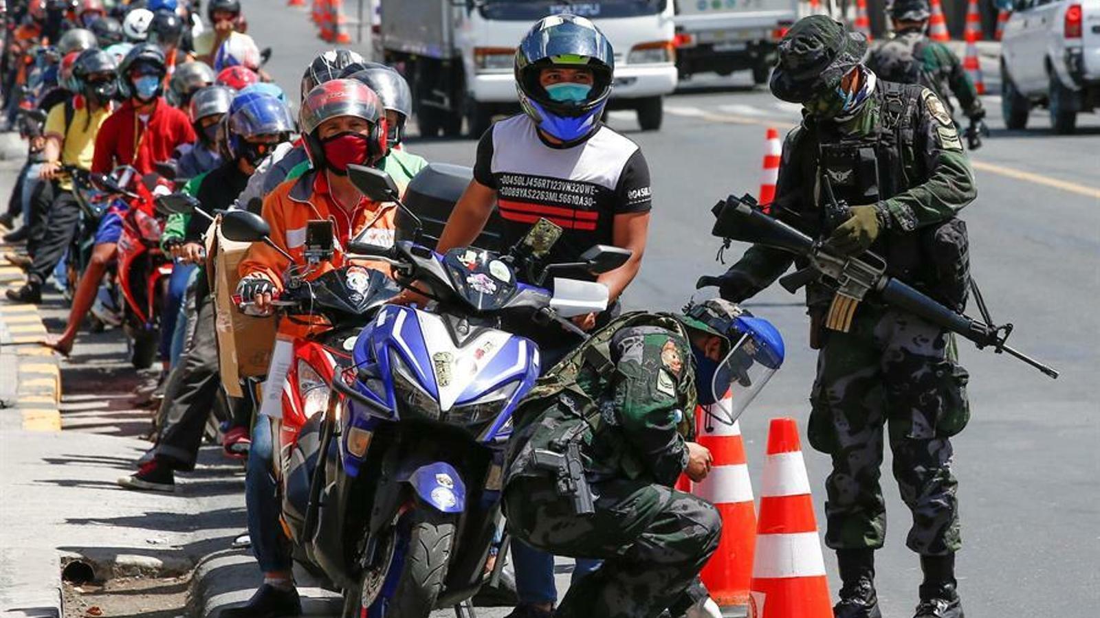 Un control militar obliga centenars de motoristes a esperar en una llarga cua, a l'àrea metropolitana de Manila