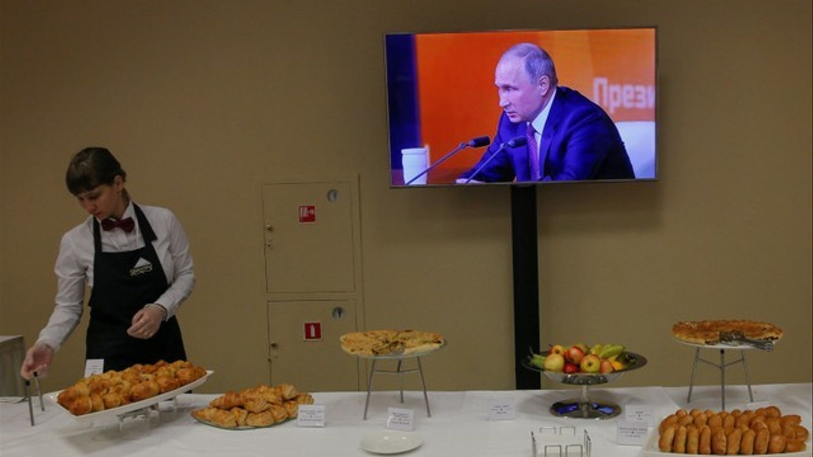 Una cambrera serveix davant d'una pantalla amb Vladímir Putin en la seva conferència anual, a Moscou.