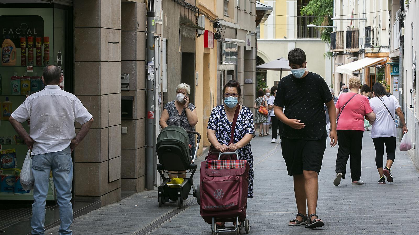 Gent passejant amb mascareta per Sant Feliu de Llobregat aquest dilluns, 20 de juliol, després que el Govern decretés mesures de seguretat extra per contenir l'avenç del coronavirus a la ciutat