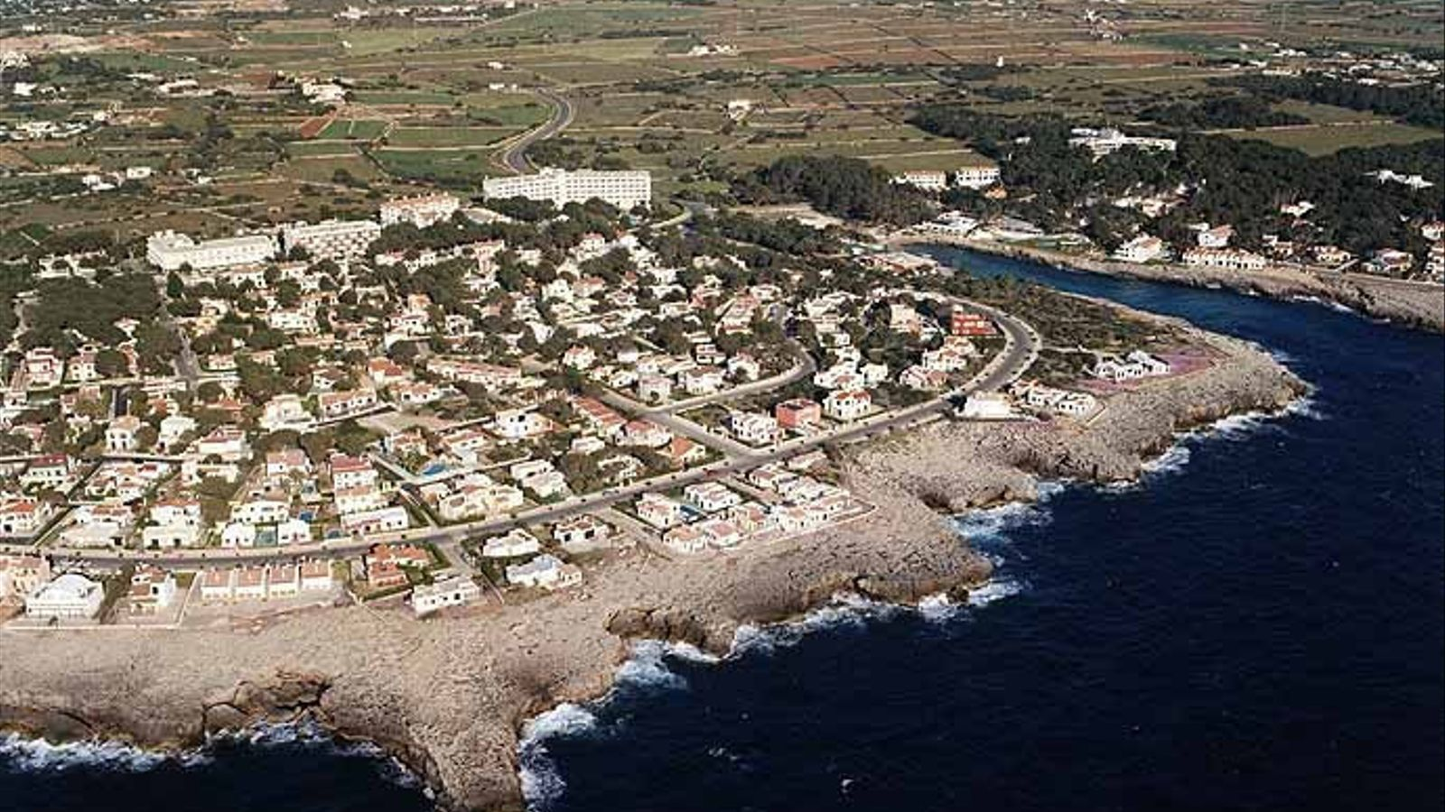 Foto aèria de Cala Blanca, a Menorca, on habitatges i vials estan construïts sobre cinc coves.