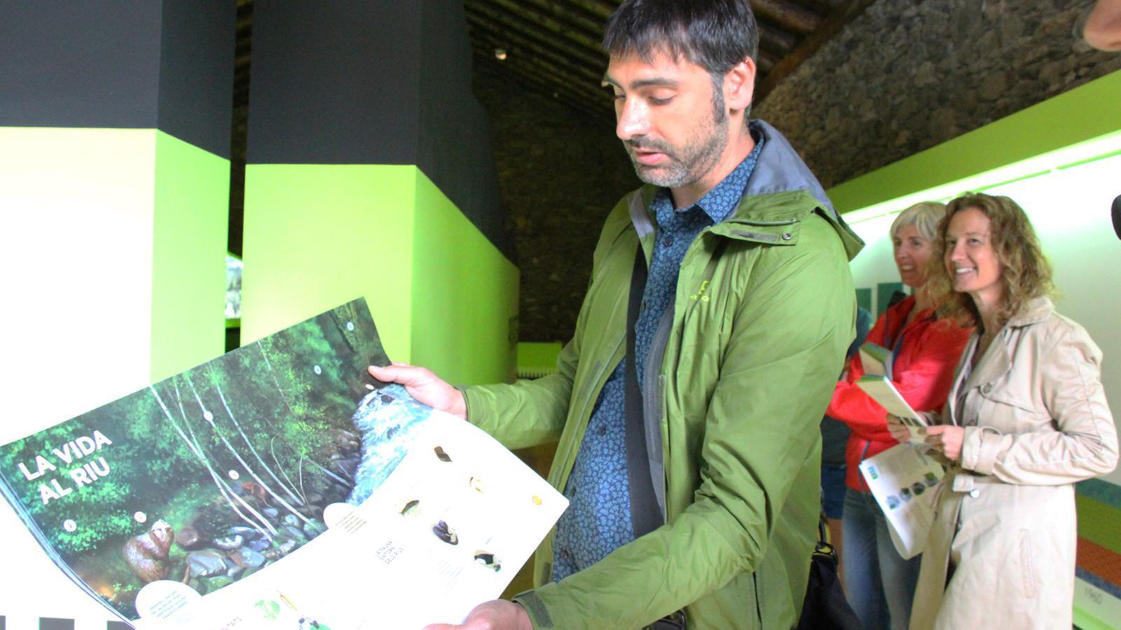 El responsable del Centre Andorra Sostenible, Javier Gómez, mostra un pòster que s'ha editat amb informació sobre la vida al riu. / E. J. M. (ANA)