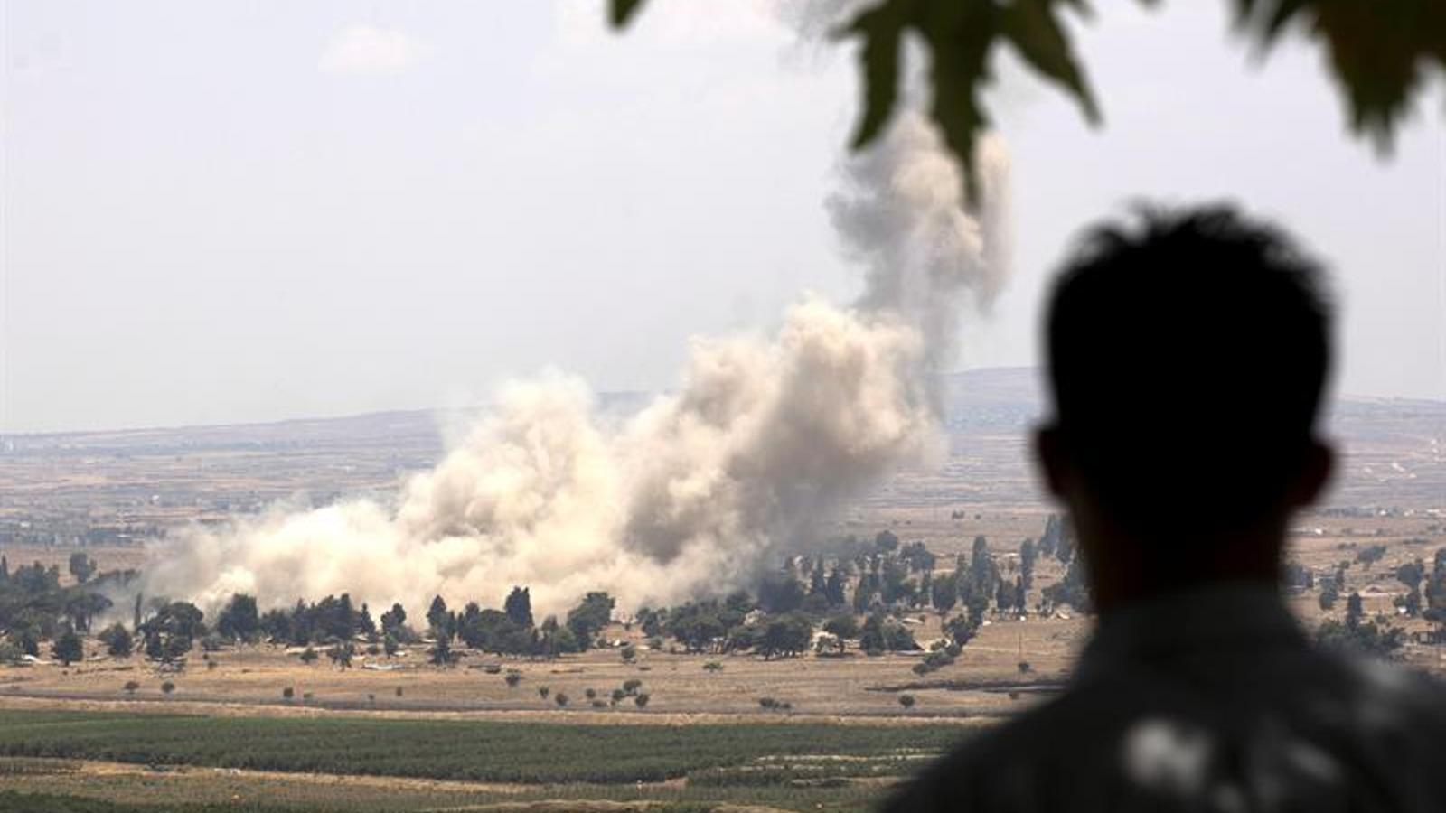 Un home observant la destrucció controlada dels dipòsits de munició dels rebels a la ciutat de Quneitra abans d'agafar l'autobús cap els Alts del Golan