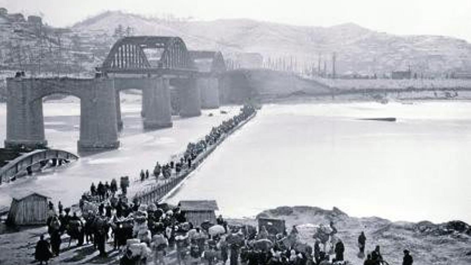 PEREGRINATGE. Refugiats coreans travessen el riu a través d'un pas provisional, construït al costat del tram danyat del pont.