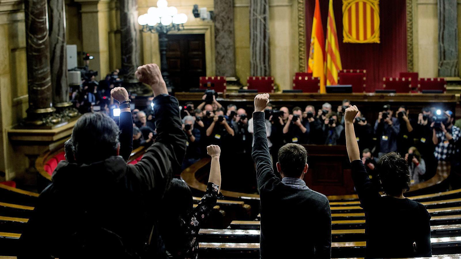 Els quatre diputats de la CUP als seus escons de l'hemicicle del Parlament.