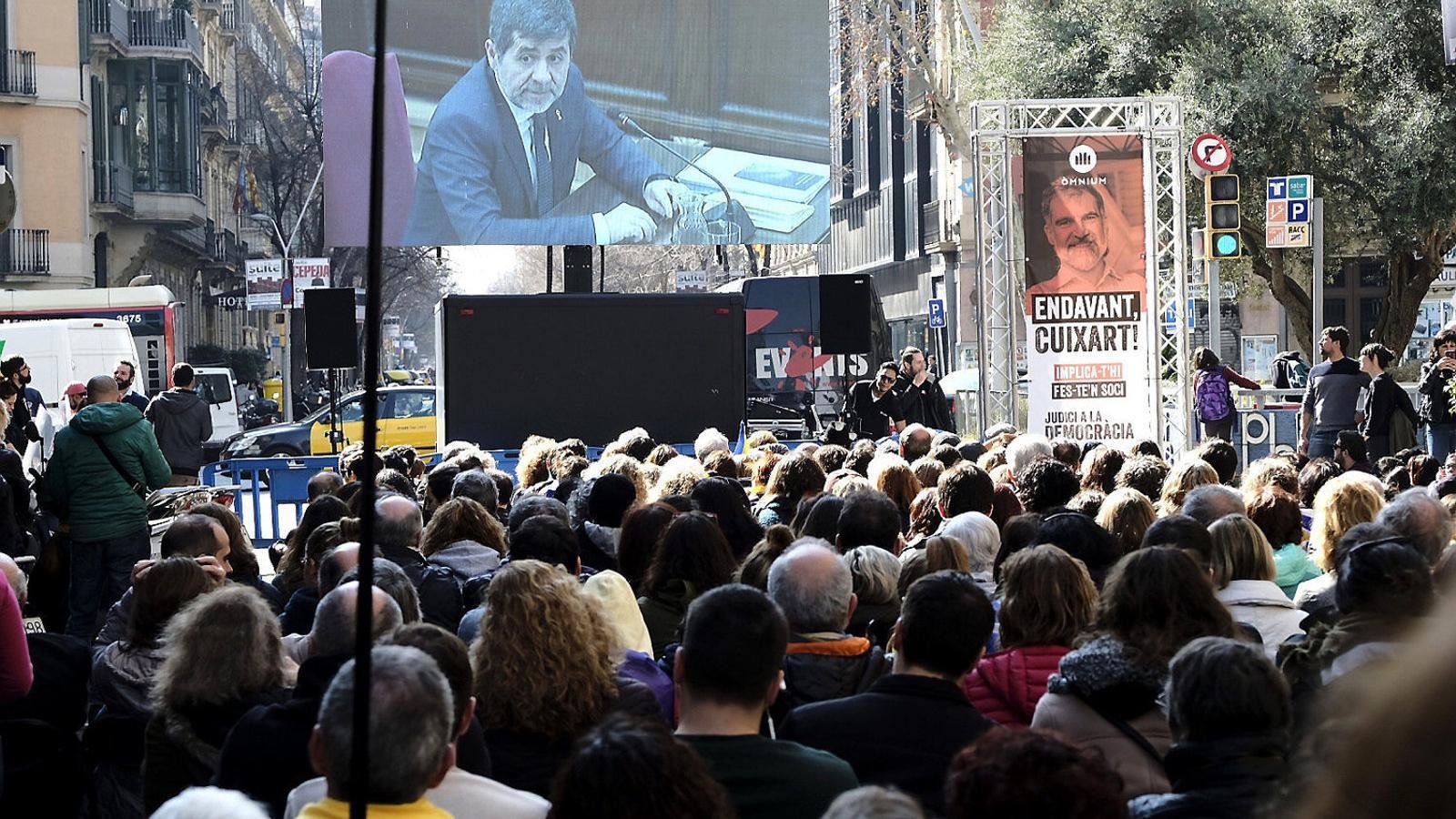 Centenars de persones observant davant la seu d'Òmnium la intervenció de Jordi Sànchez.