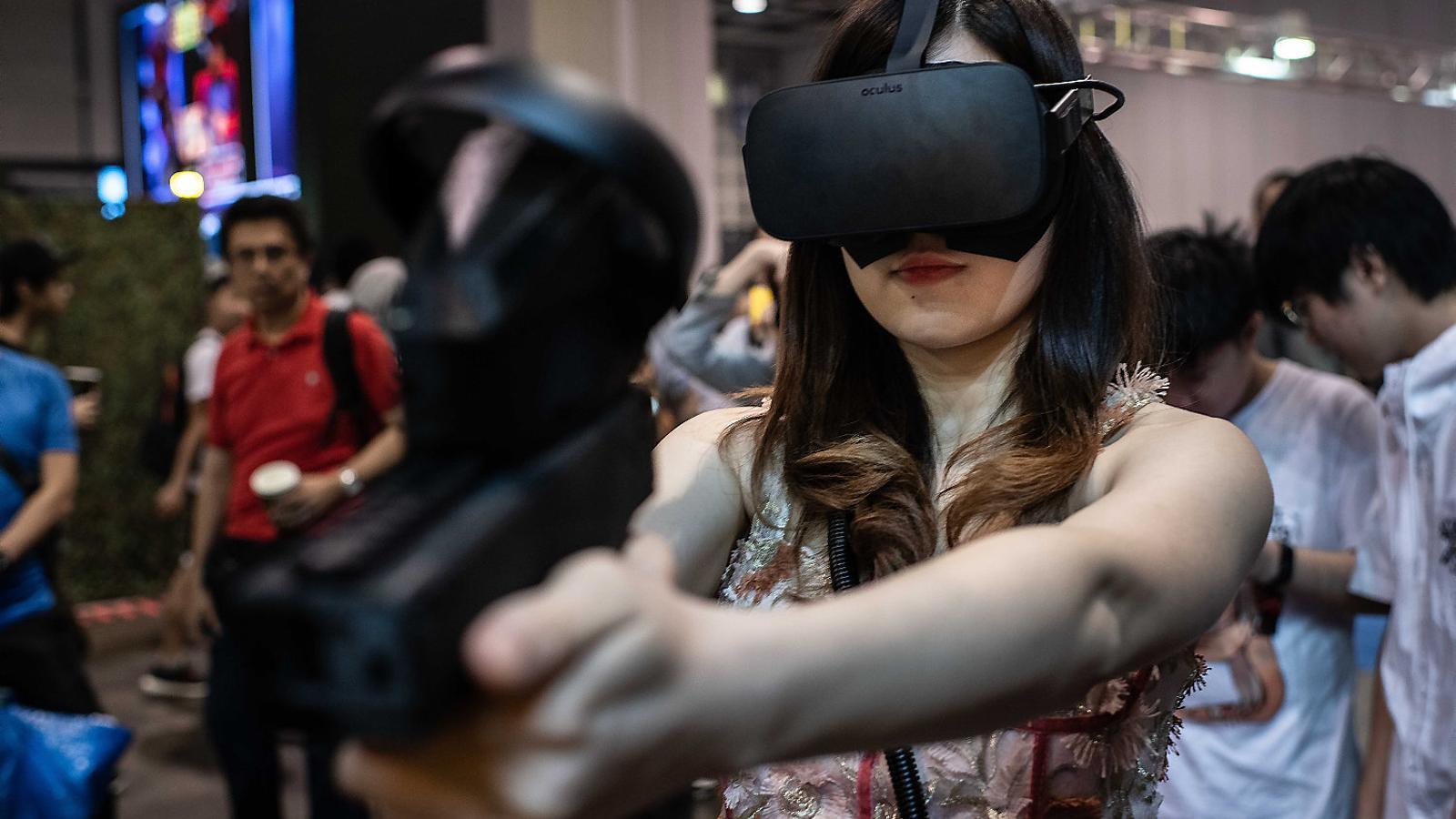 Una noia jugant a un videojoc de realitat virtual durant un festival a Hong Kong.