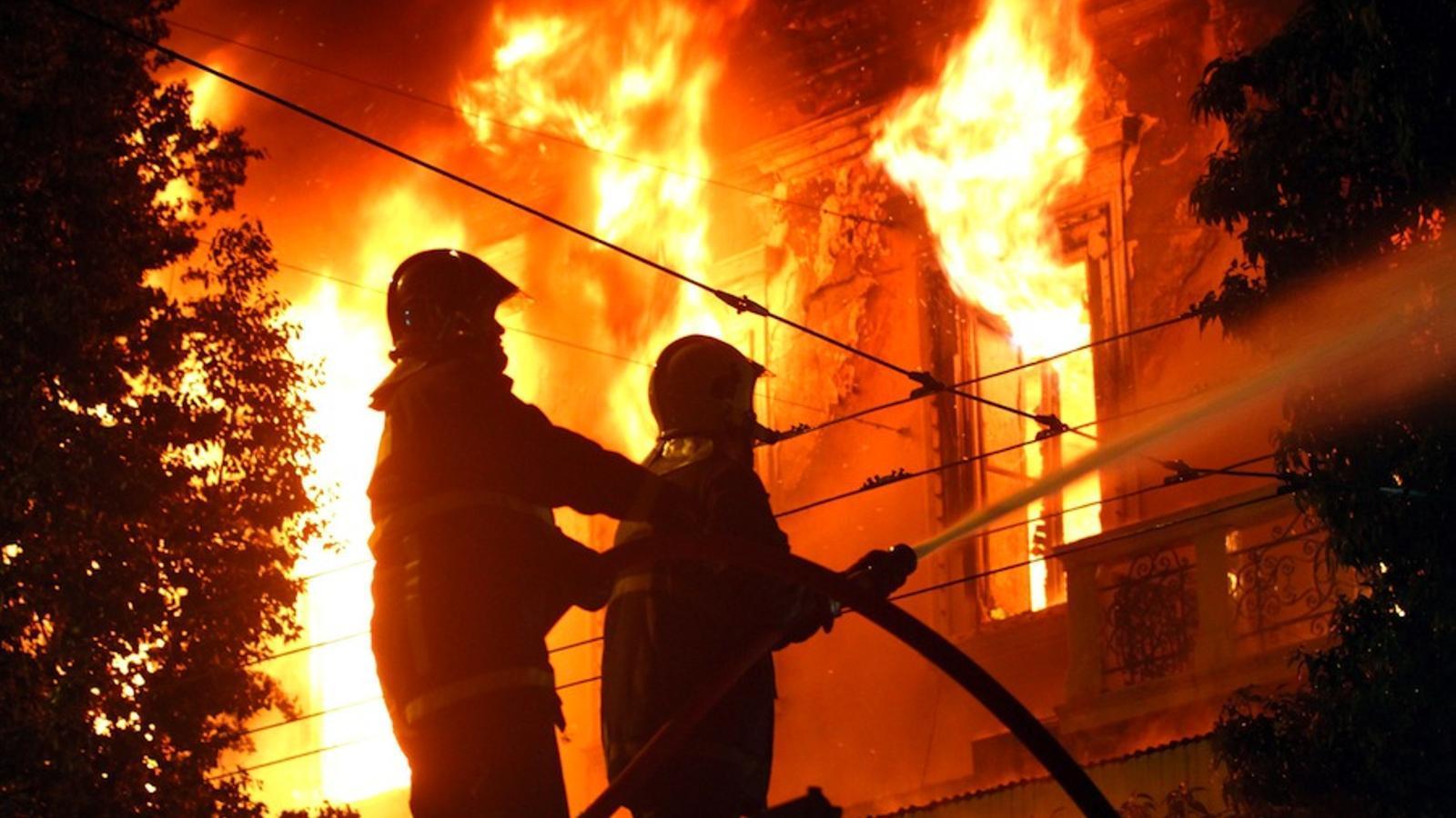 Els bombers intenten apagar un edifici incendiat / EFE