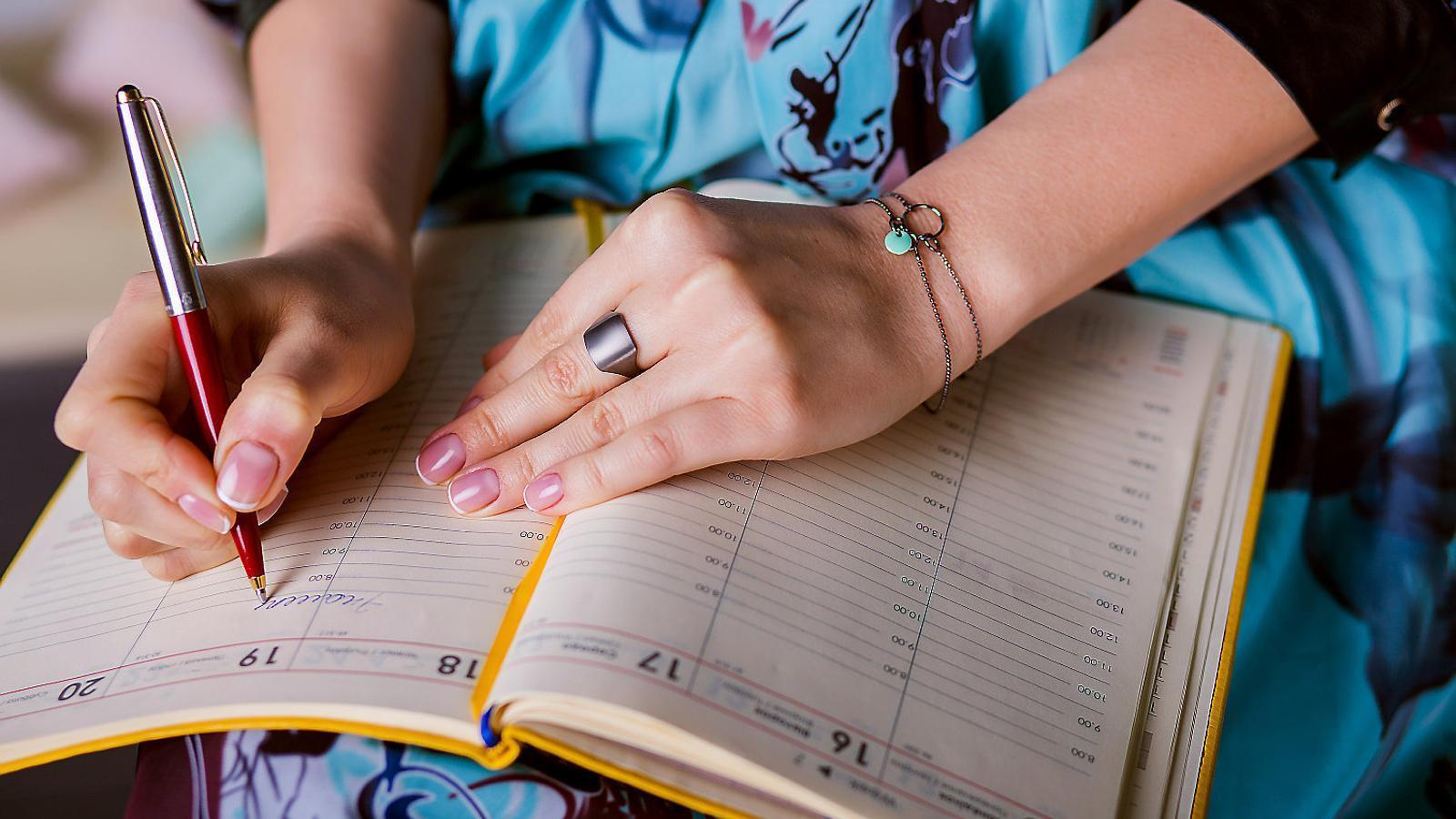 Persona usando una agenda de papel