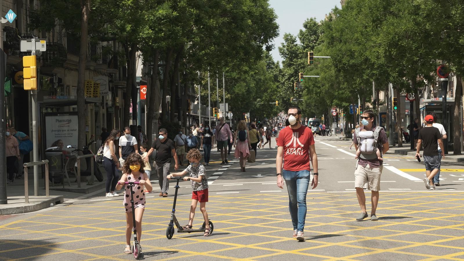 Persones passejant pel carrer tallat a Barcelona de la Creu Coberta aquest dissabte.