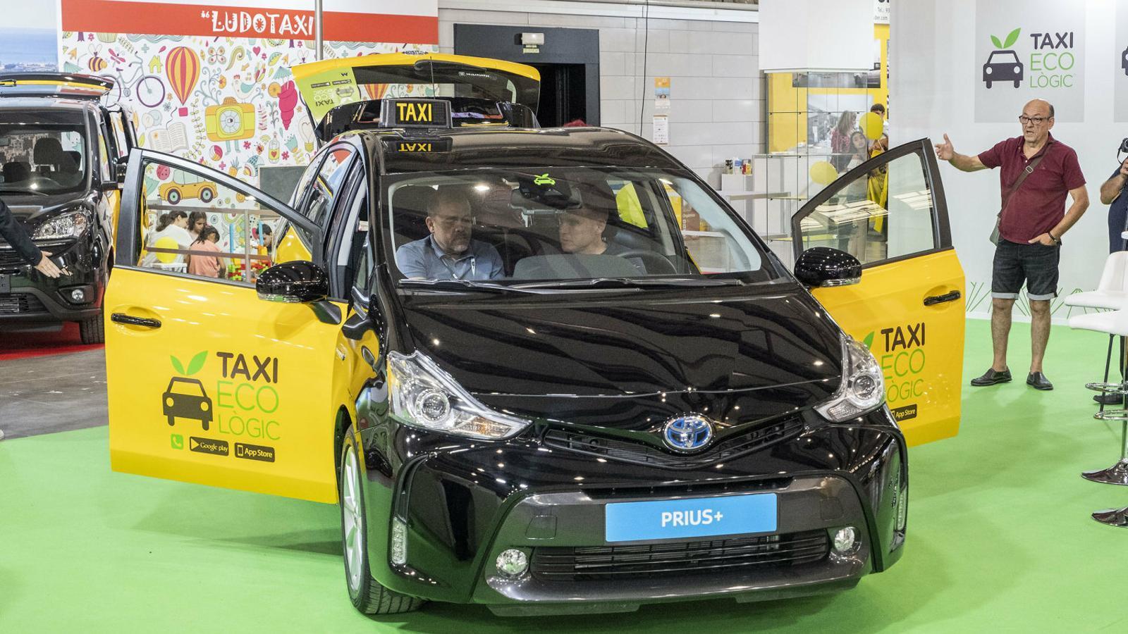 Un taxista interessat en un dels cotxes híbrids que hi havia exposats a la fira.