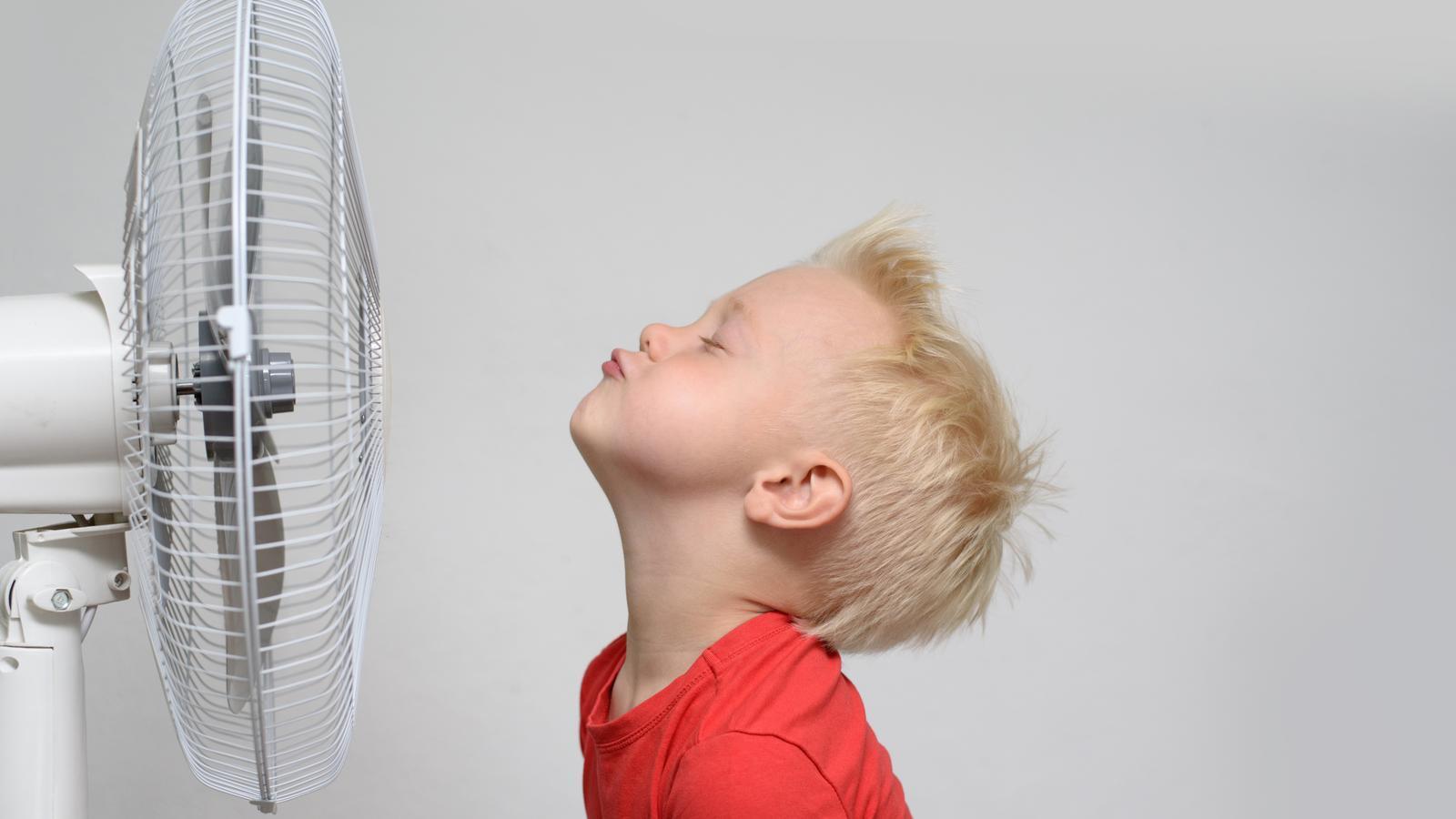 Un nen davant d'un ventilador