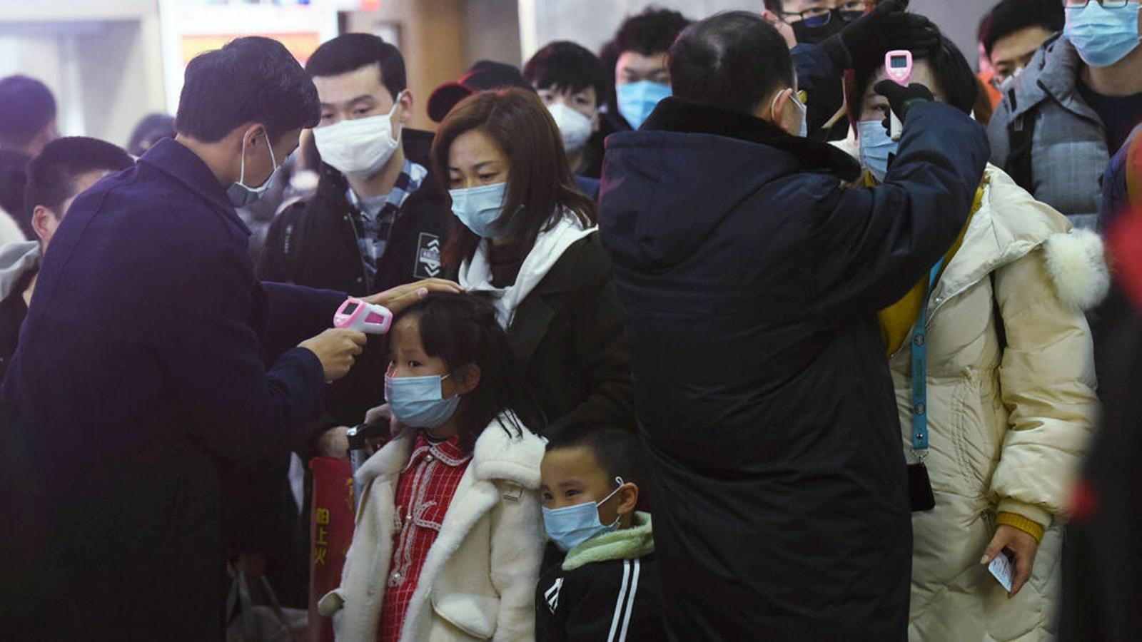 Personal prenent la temperatura a passatgers que arriben de Wuhan (la Xina). / REUTERS