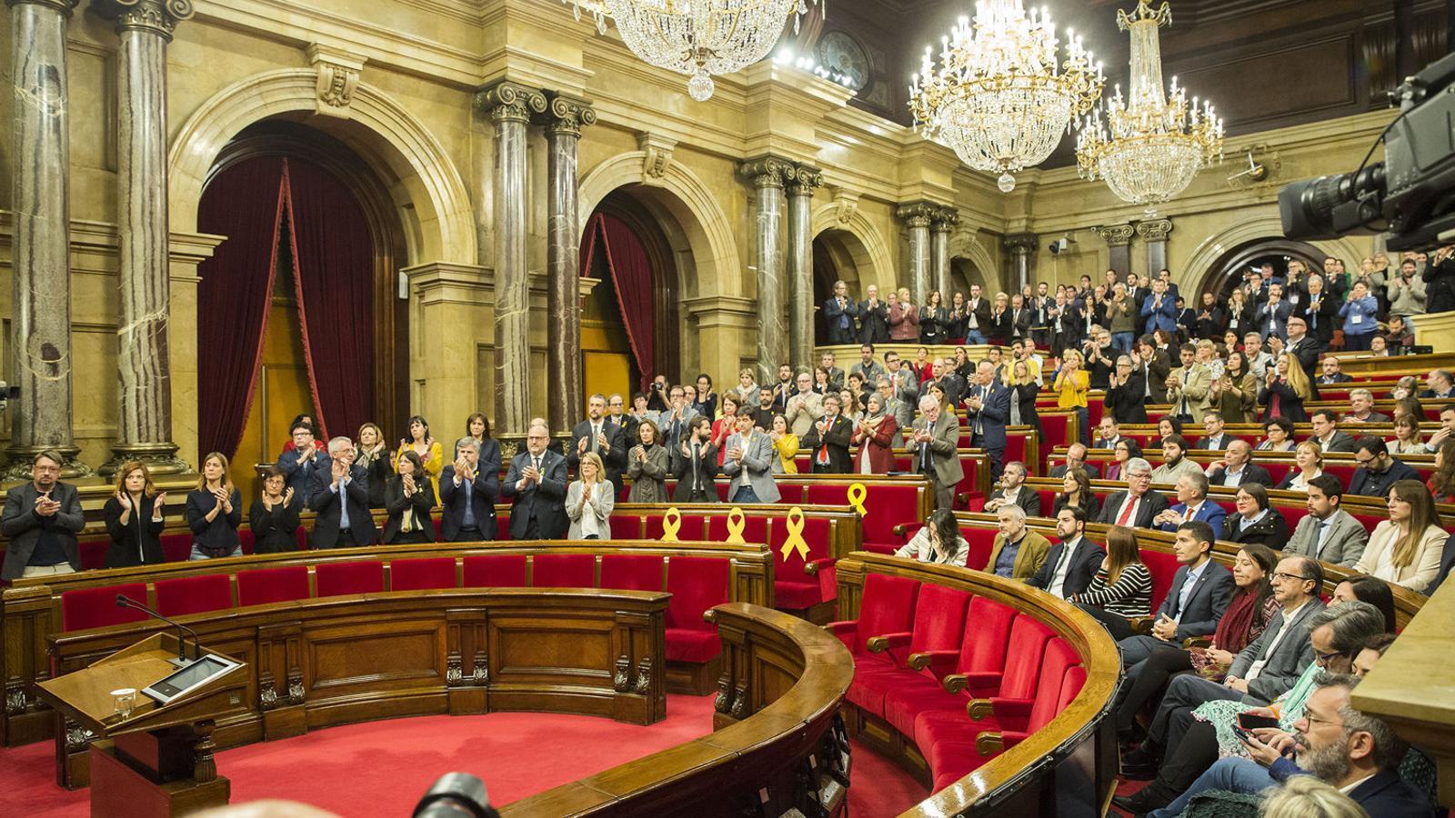 Els diputats de JxCat, ERC, els comuns i la CUP aplaudint al final del ple d'ahir al Parlament.