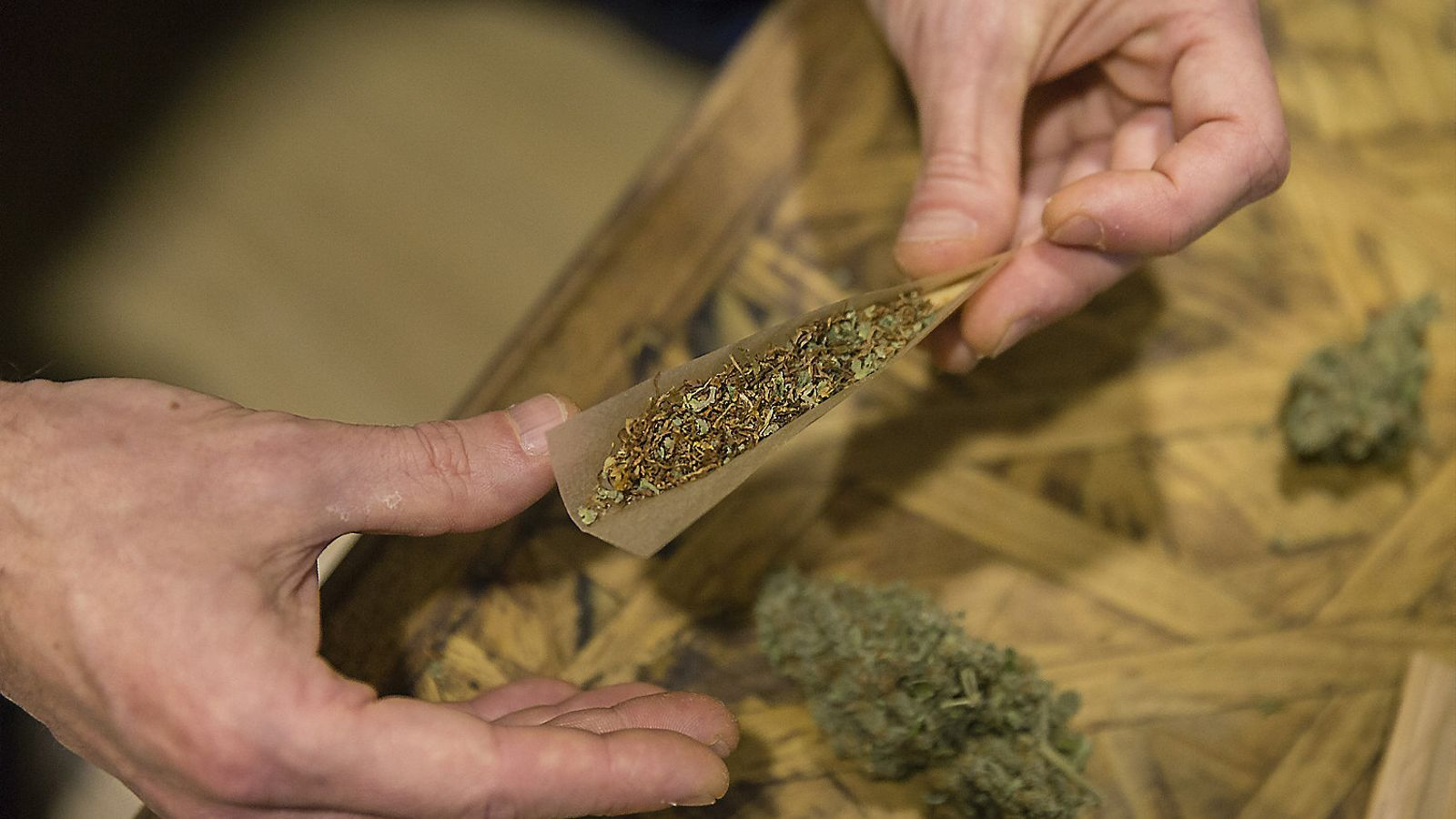 Una persona, En una imatge d'arxiu, mostrant un cigar de cànnabis a mig fer.