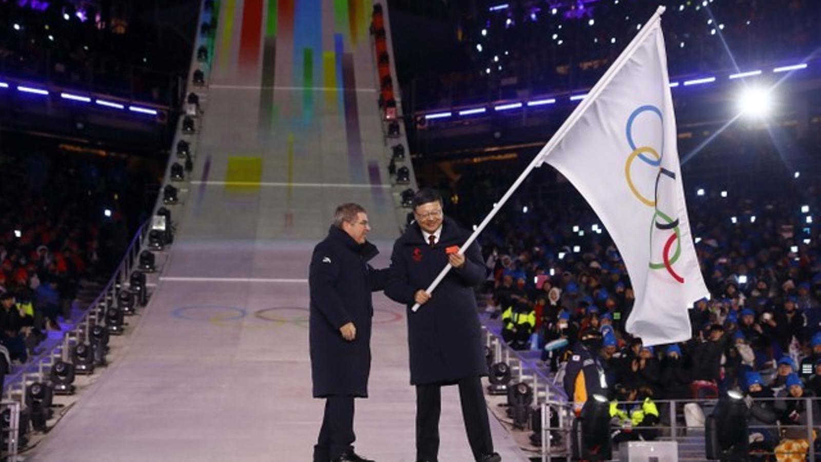 L'alcalde de Pequín pren la bandera com propera  a seu olímpica, a la cloenda dels jocs coreans.
