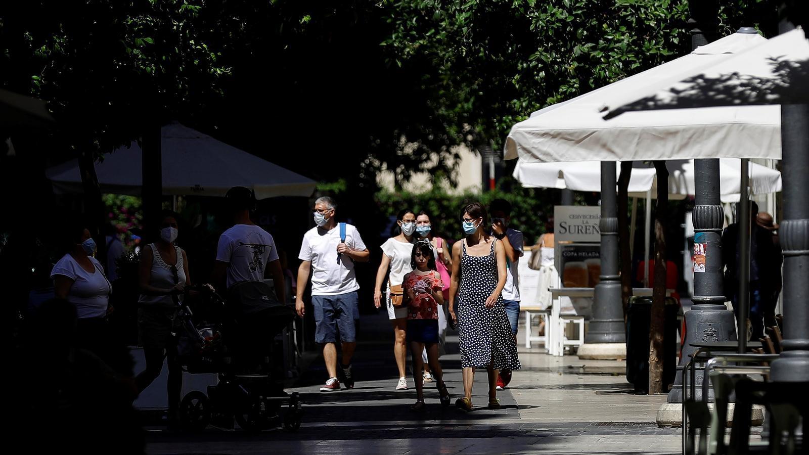 Diverses persones passegen pel centre de la ciutat de València
