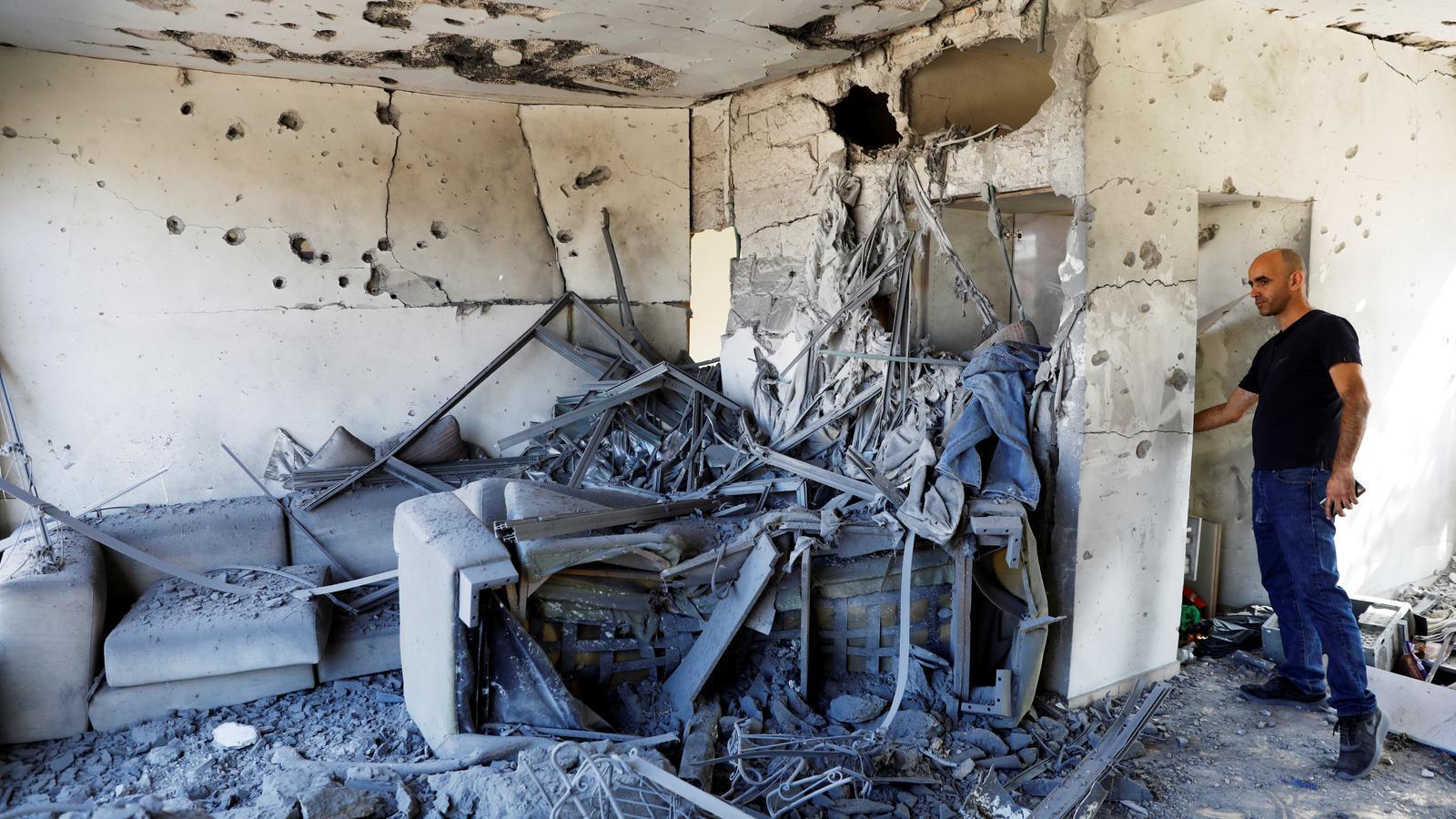 Un home observa les destrosses de casa seva a la ciutat israeliana d'Ashkelon