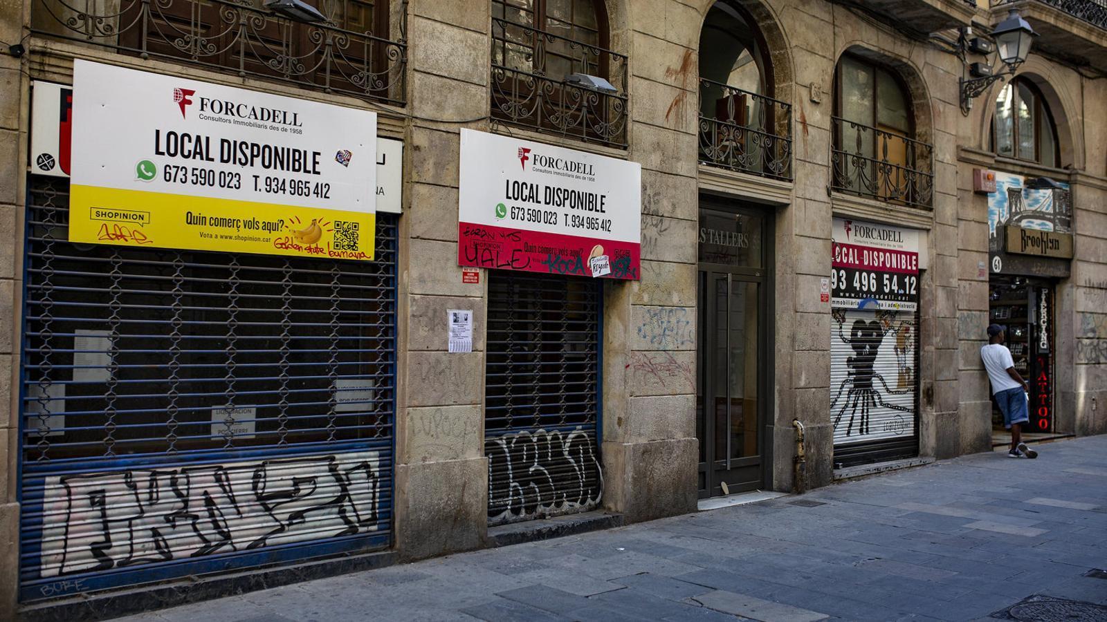 Tres locals comercials buits seguits al centre de Barcelona.