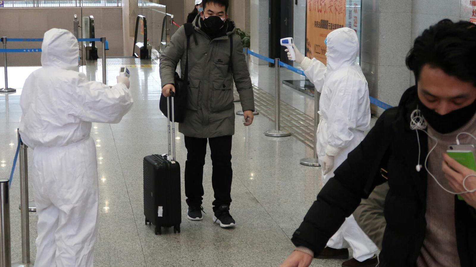 Dos sanitaris controlen la temperatura dels passatgers a l'estació de trens de Xianning per saber si tenen febre.