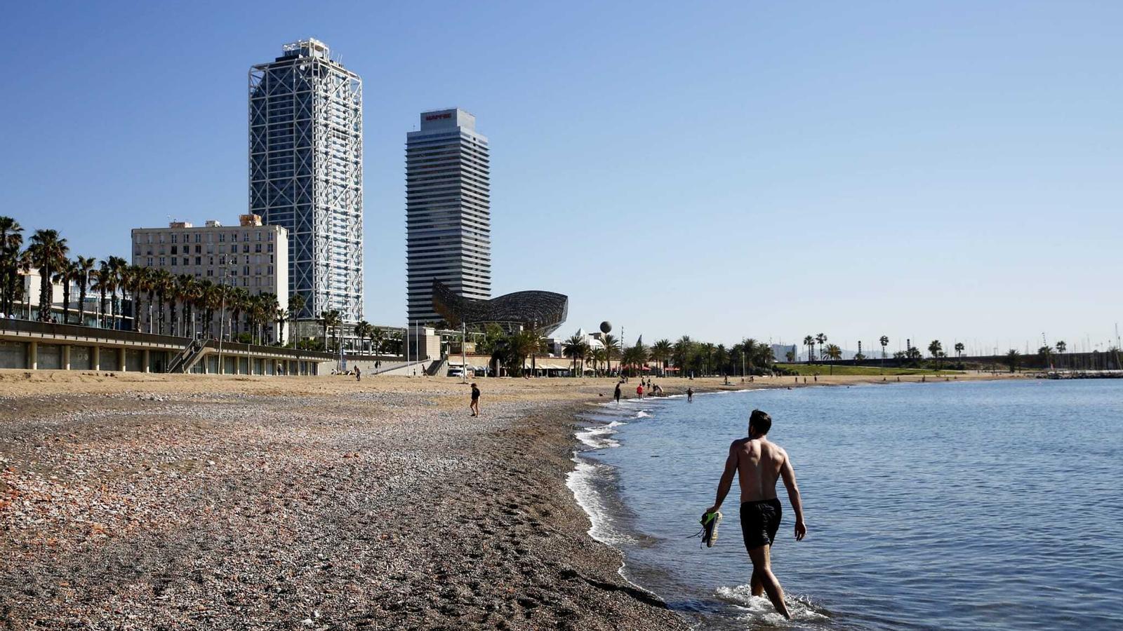 Un ciutadà passejant per la platja de Barcelona, aquest matí