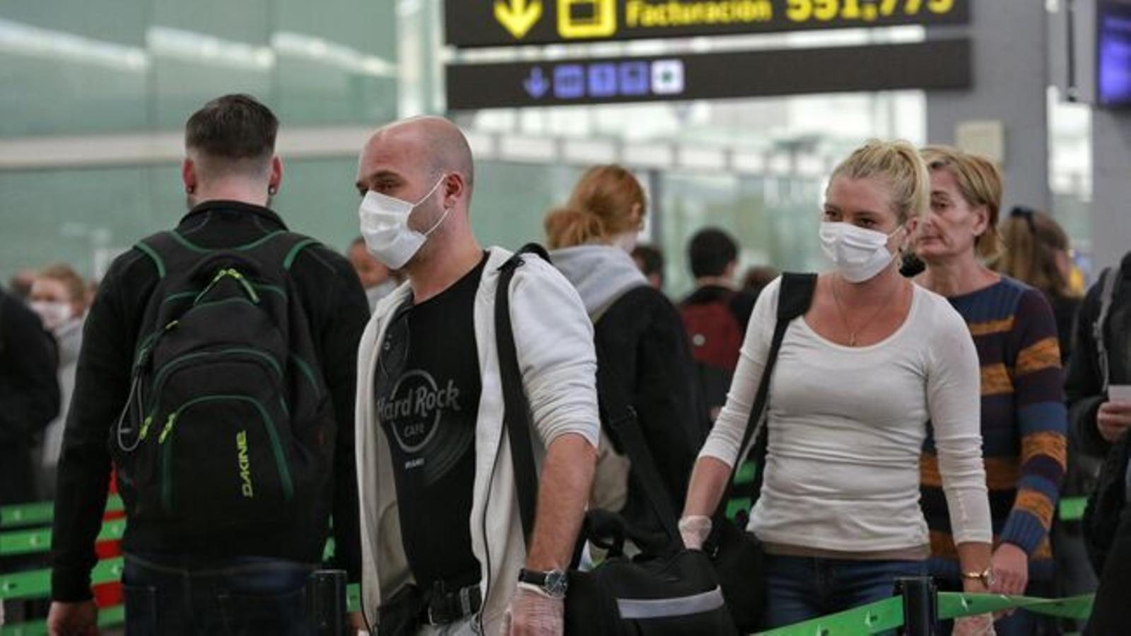 Molts del passatgers que avui circulen per l'aeroport porten mascaretes de protecció pel coronavirus / CRISTINA CALDERER