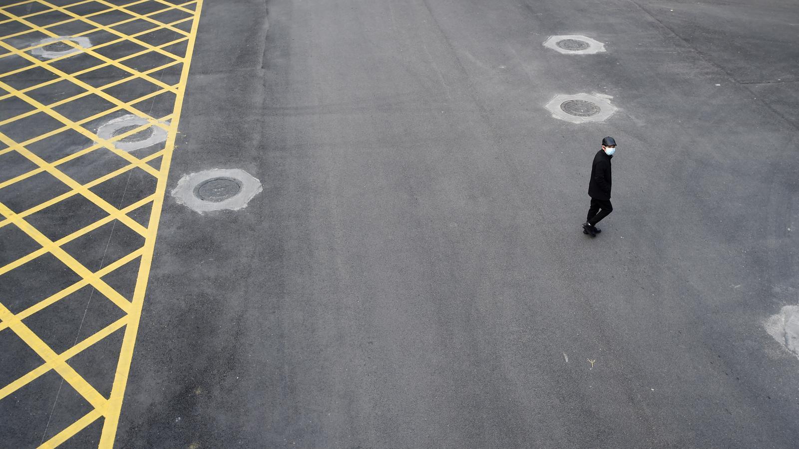 Un home creua un dels carrers buits de Wuhan.