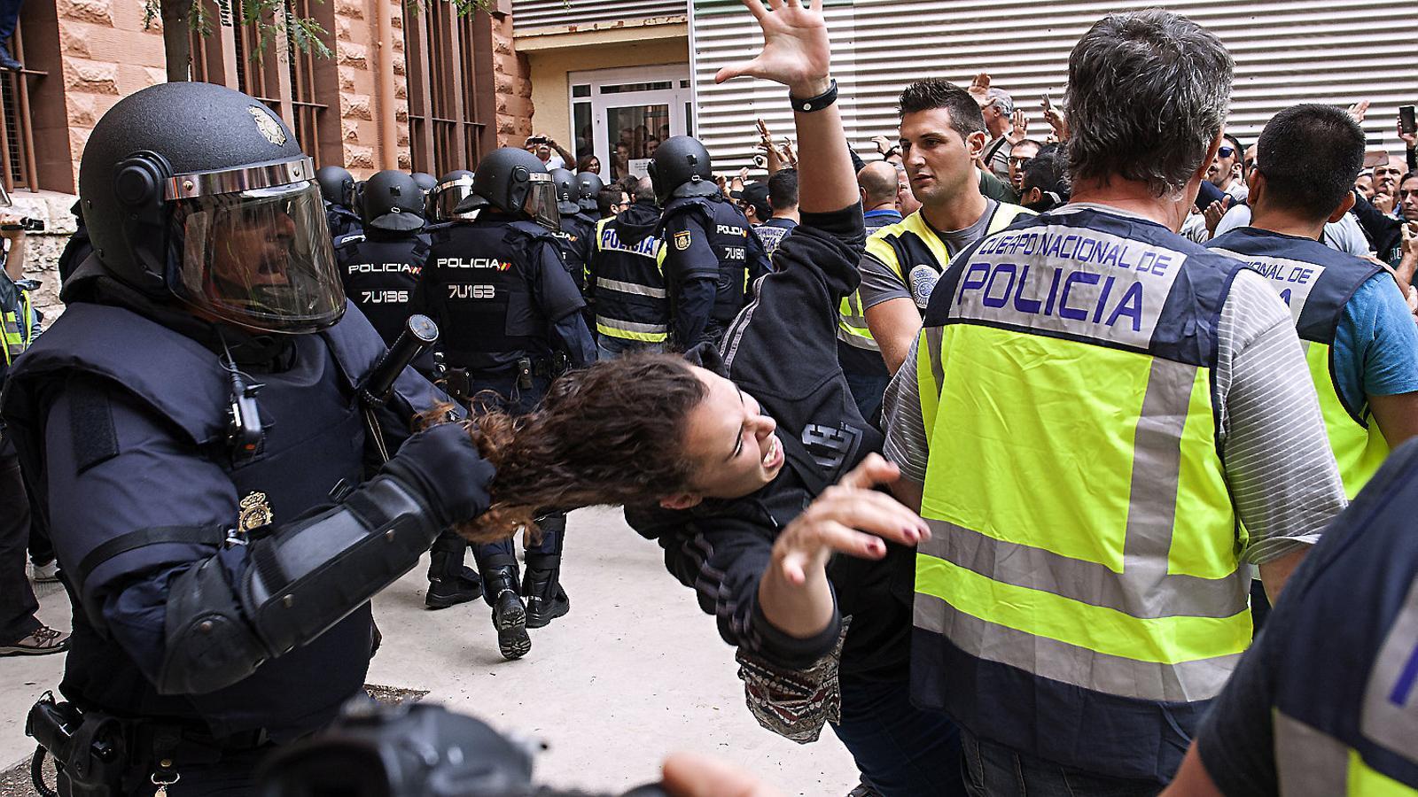 Un policia nacional estirant  pels cabells una votant a Tarragona.