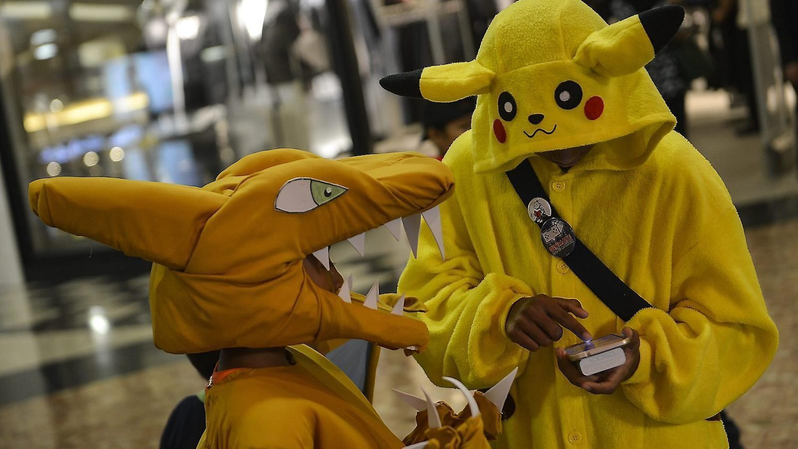 Dos nois disfressats de charizard i pikachu en un concurs de disfresses de Pokémon a Sunway, a Malàisia.