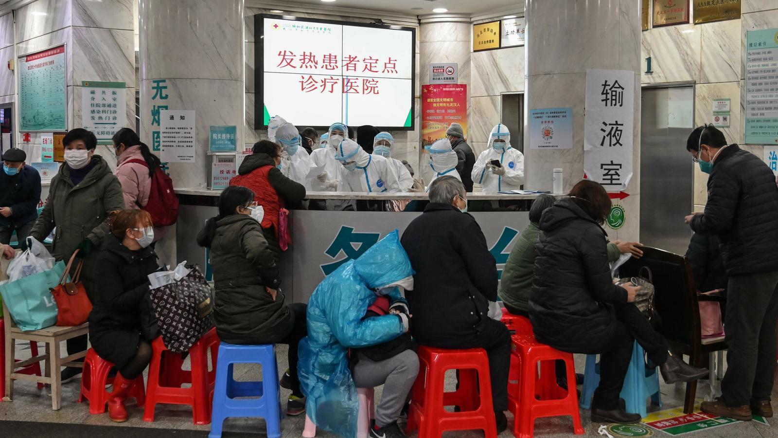 Gent esperant al personal mèdic, al fons amb roba de protecció, a l'Hospital de la Creu Roja de Wuhan