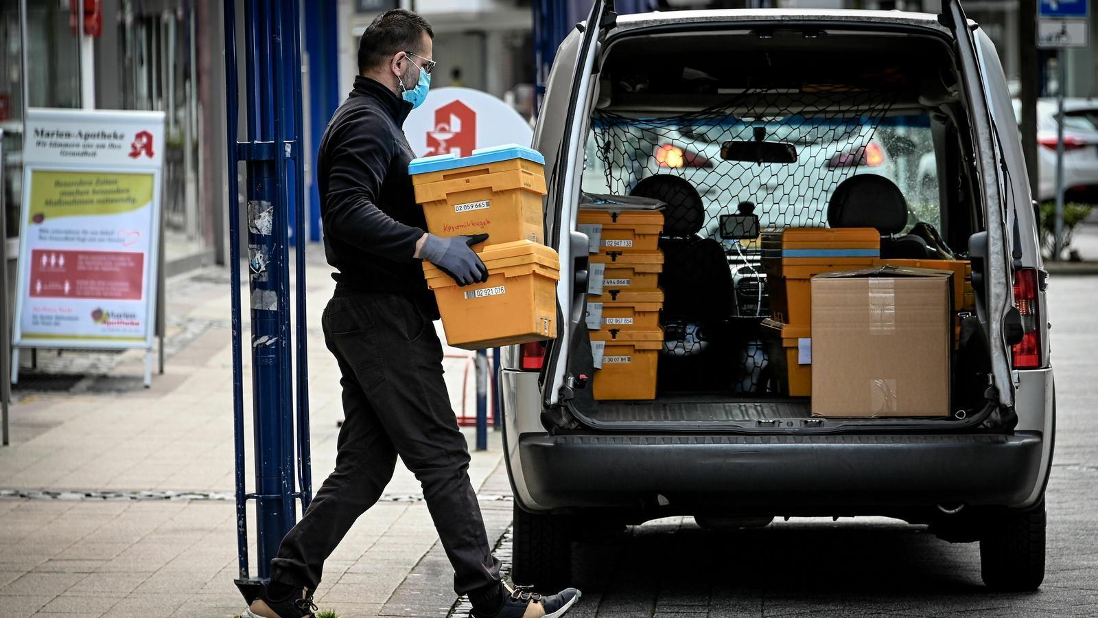 Un empleat del servei de missatgeria d'una farmàcia carrega caixes a Heinsberg, Alemanya