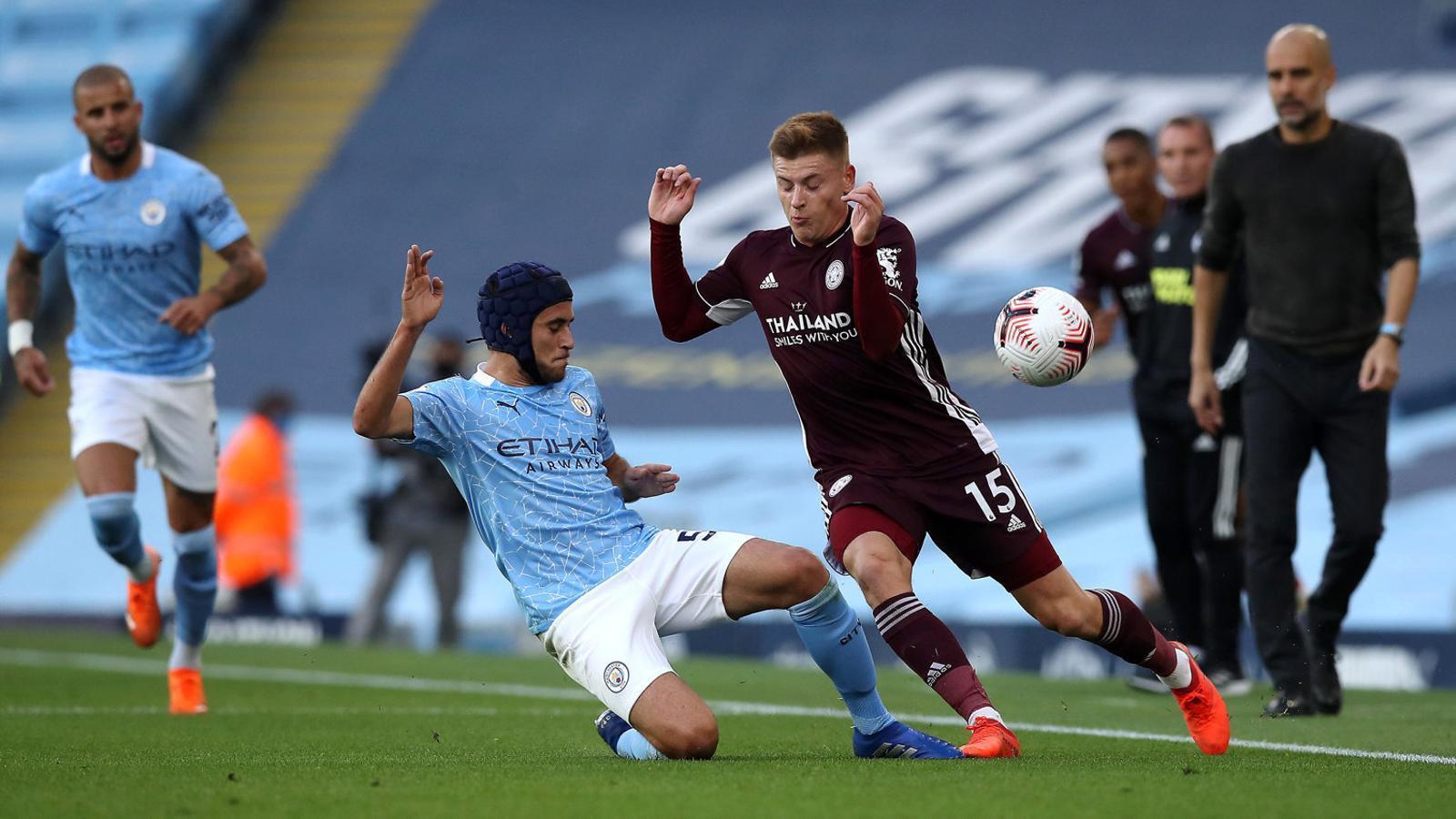 Eric García, amb un casc protector, pugnant per una pilota en un partit amb el Manchester City, amb Pep Guardiola seguint la jugada en segon pla.