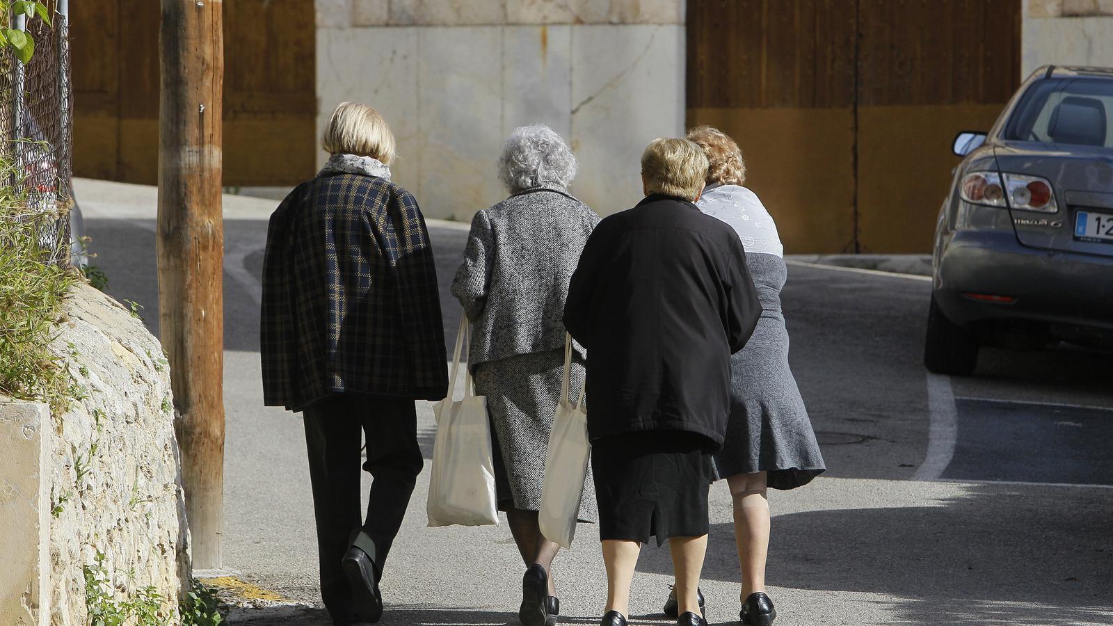 Gent caminant per un carrer.