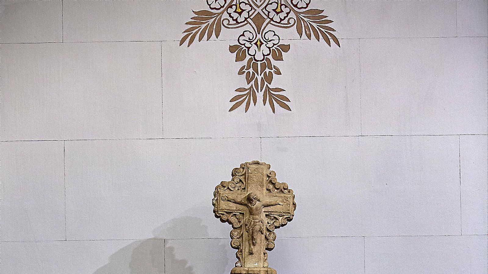 La creu de terme que hi ha dins la sala de plens de la seu del districte de Sants-Montjuïc i que reprodueix la que estava sota un cobert.