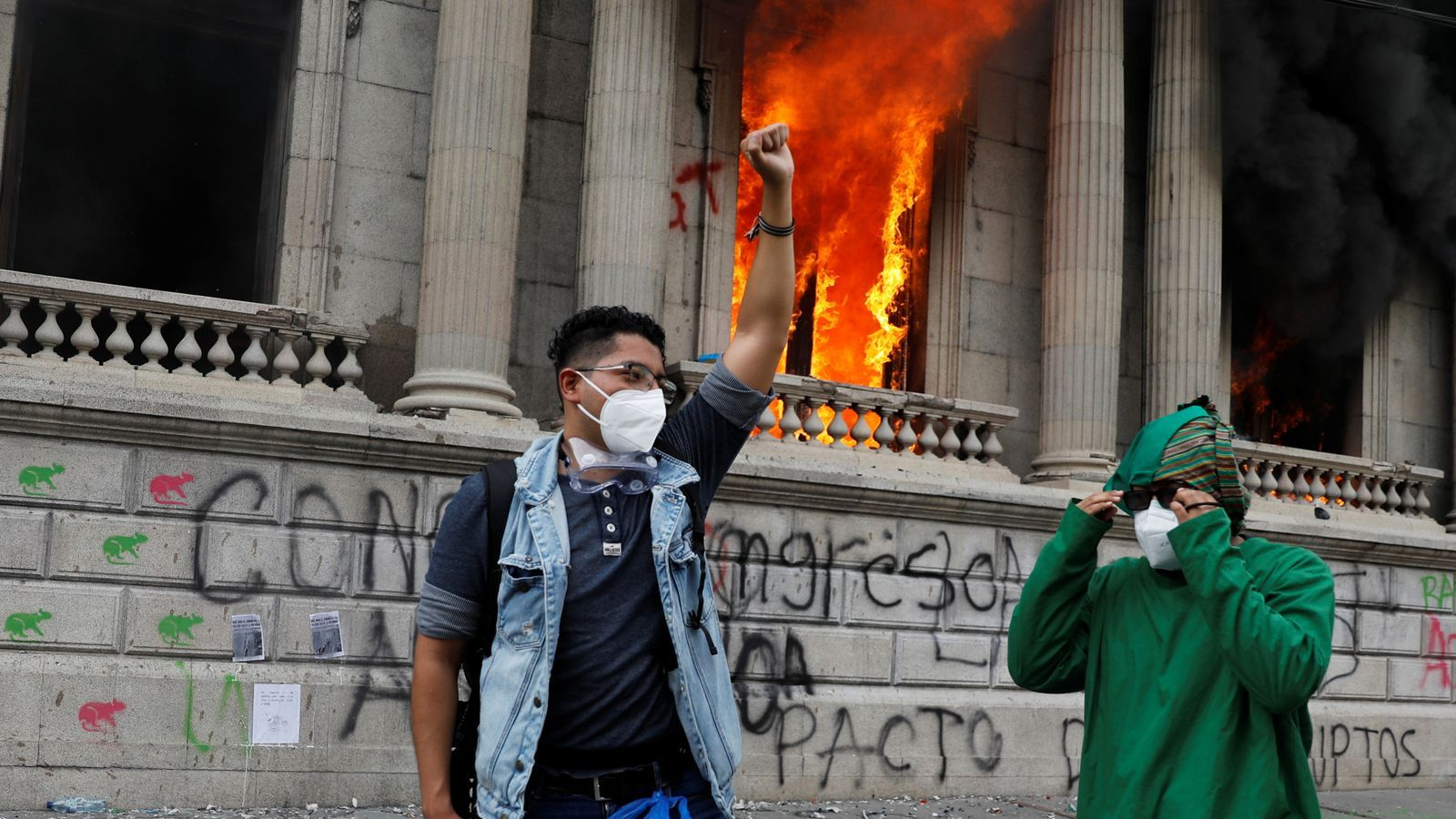 Dos manifestants davant la seu del parlament, en flames.