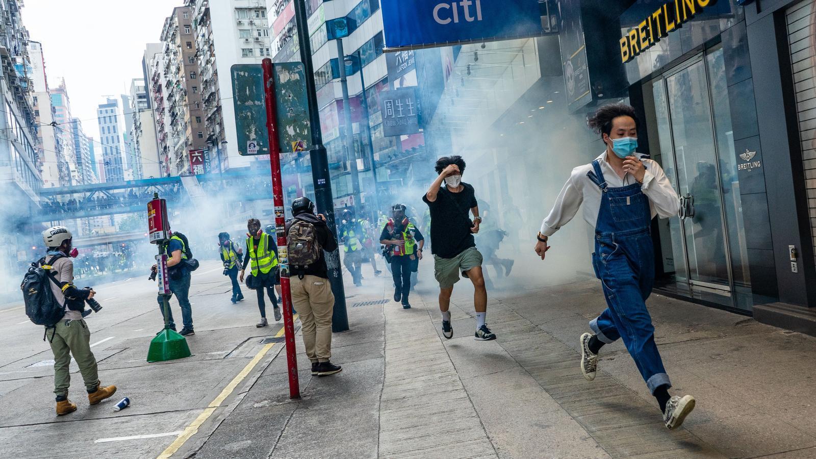 Diversos manifestants fugen dels gasos lacrimògens llançats per la policia