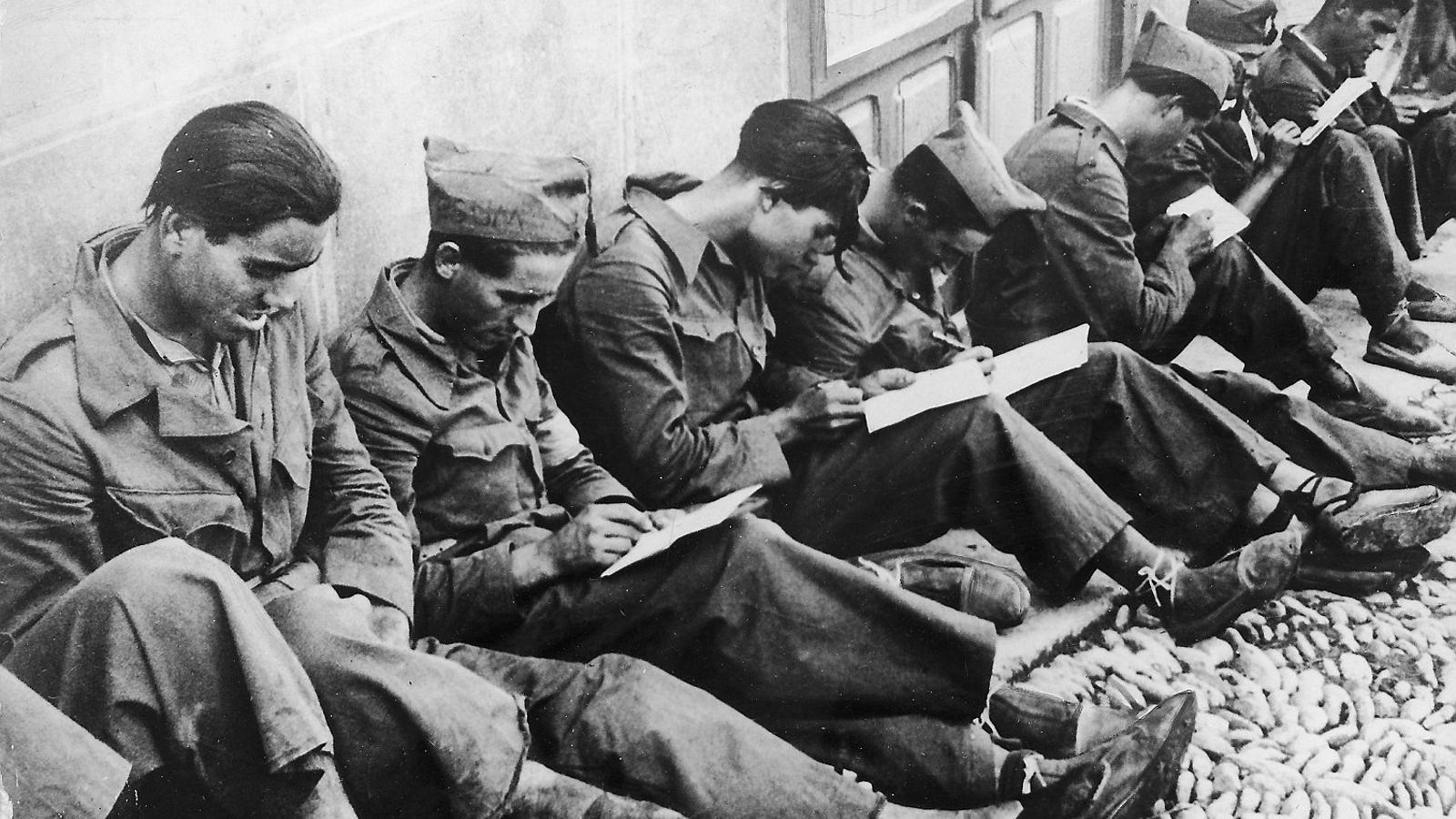 Un grup de soldats escrivint cartes i diaris.