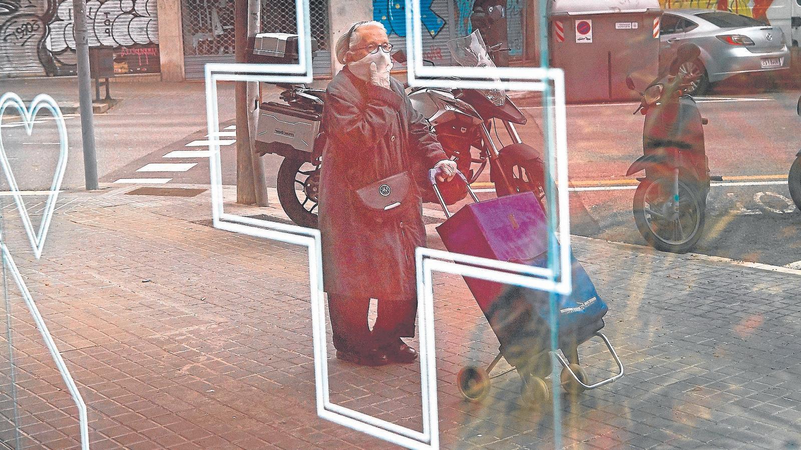Una dona gran va a comprar amb el carretó i es cobreix la cara amb una mascareta al barri de la Sagrada Família de Barcelona.