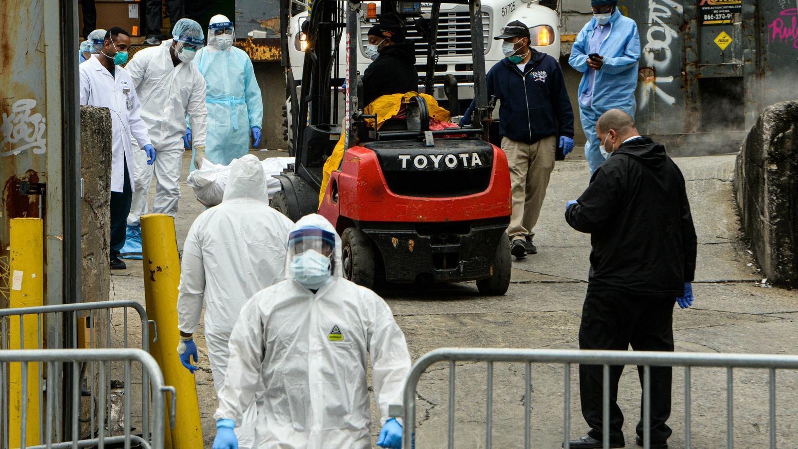 Un operari trasllada cossos sense vida de pacients a un camió frigorífic al Brooklyn Hospital Center de Nova York